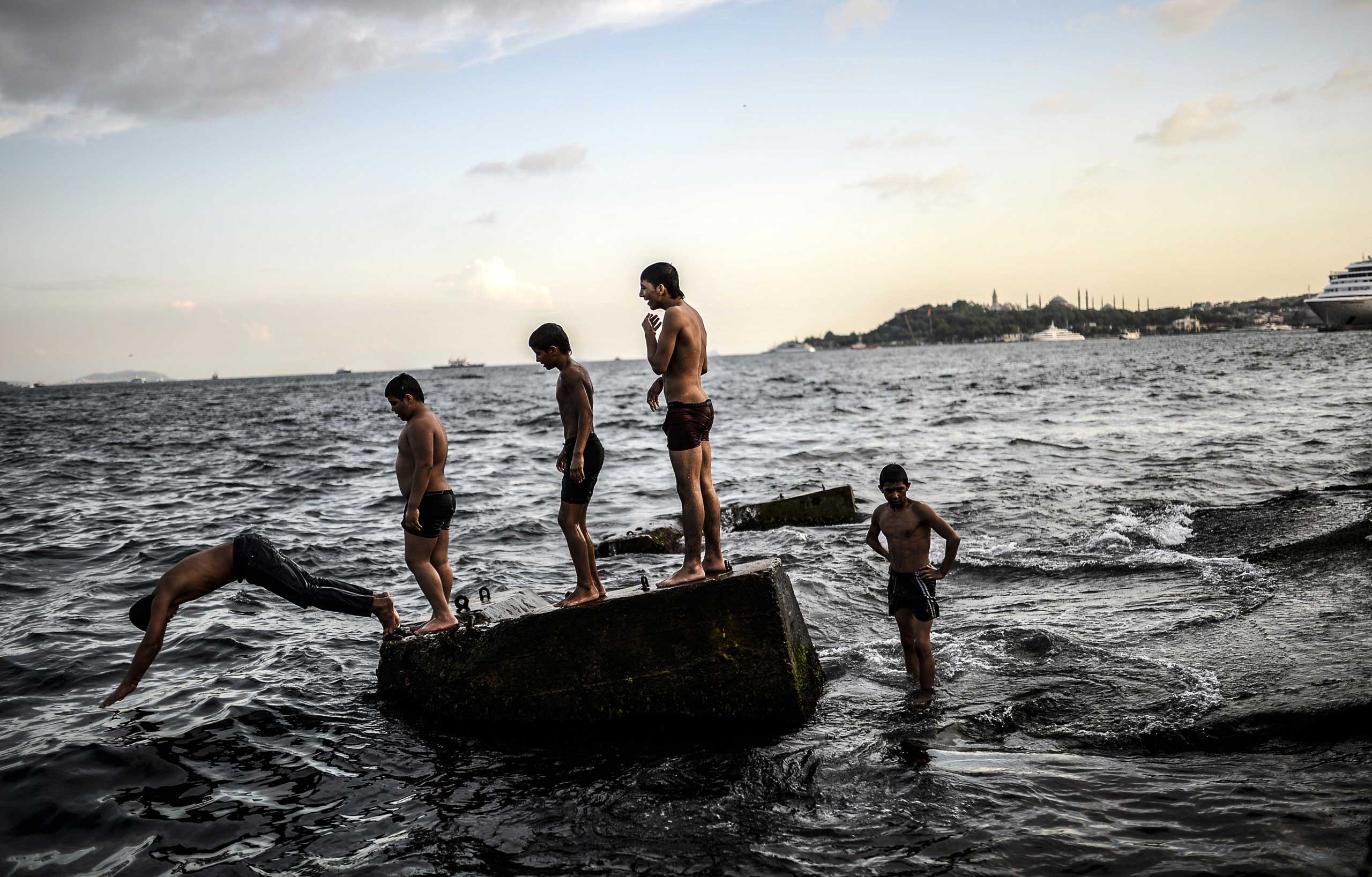 Syrian refugee boys swim in the Bosphorus on Aug. 8, 2014 at Kabatas in Istanbul, Turkey.