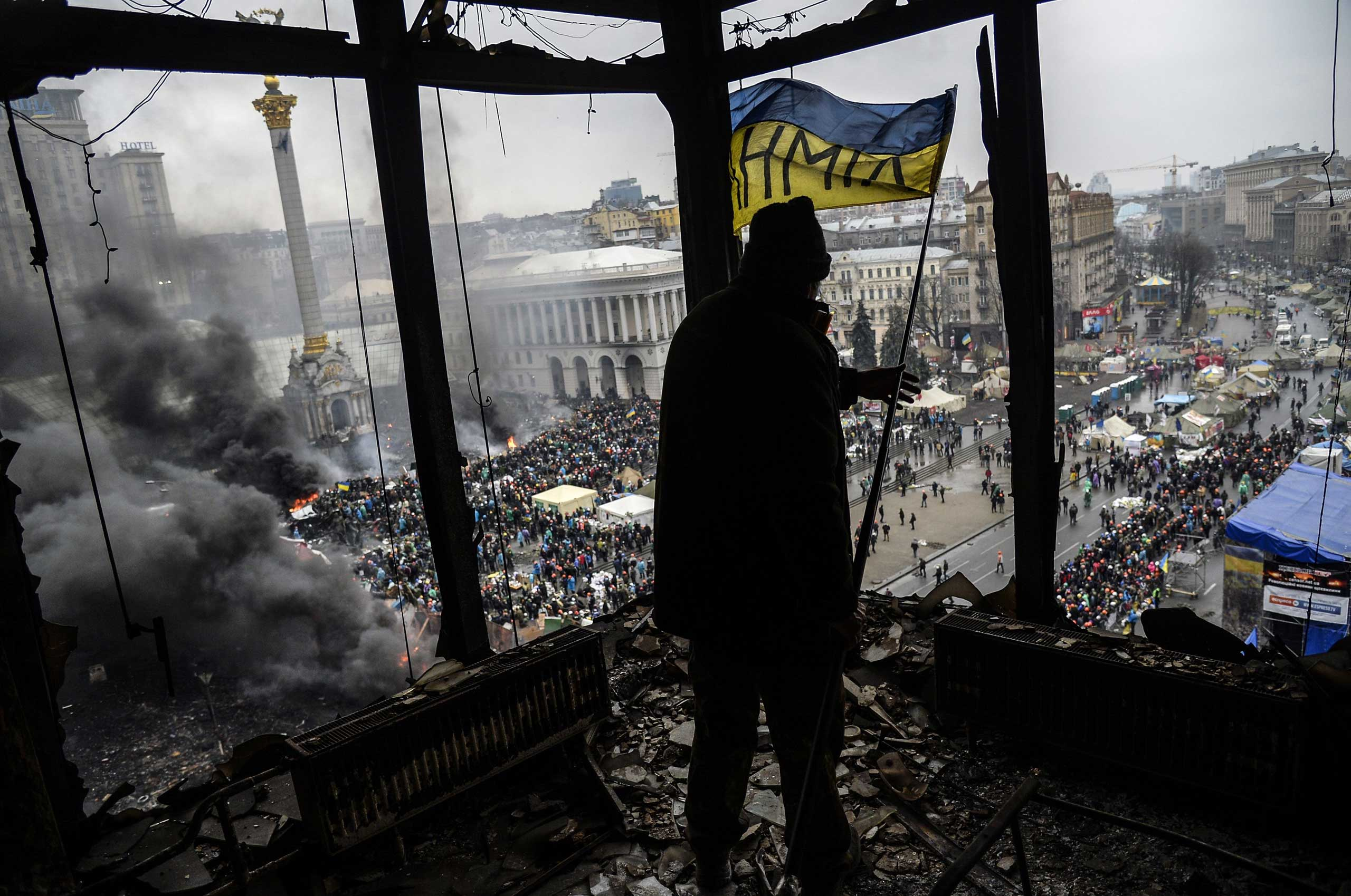 A protester holds an Ukranian national flag from a burned building during a face-off against police on Feb. 20, 2014 in Kiev, Ukraine.