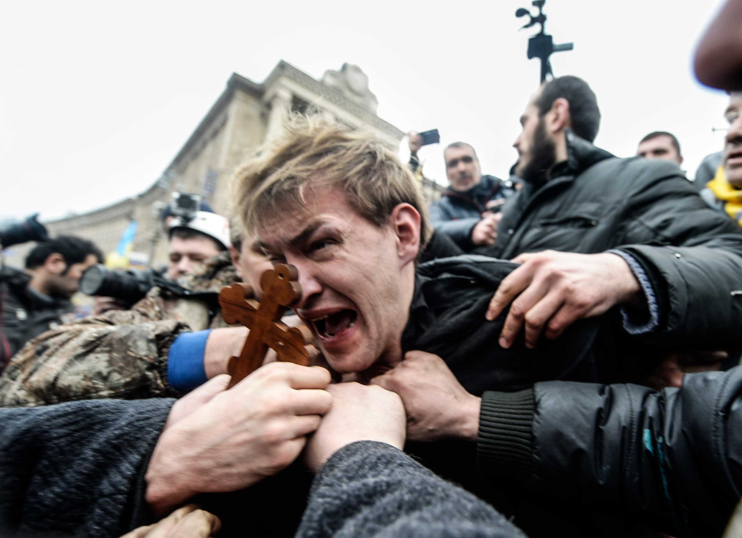 An alleged sniper (C) and member of the pro-government forces is beaten by anti-government protestors in Kiev, Ukraine, on Feb. 22, 2014.