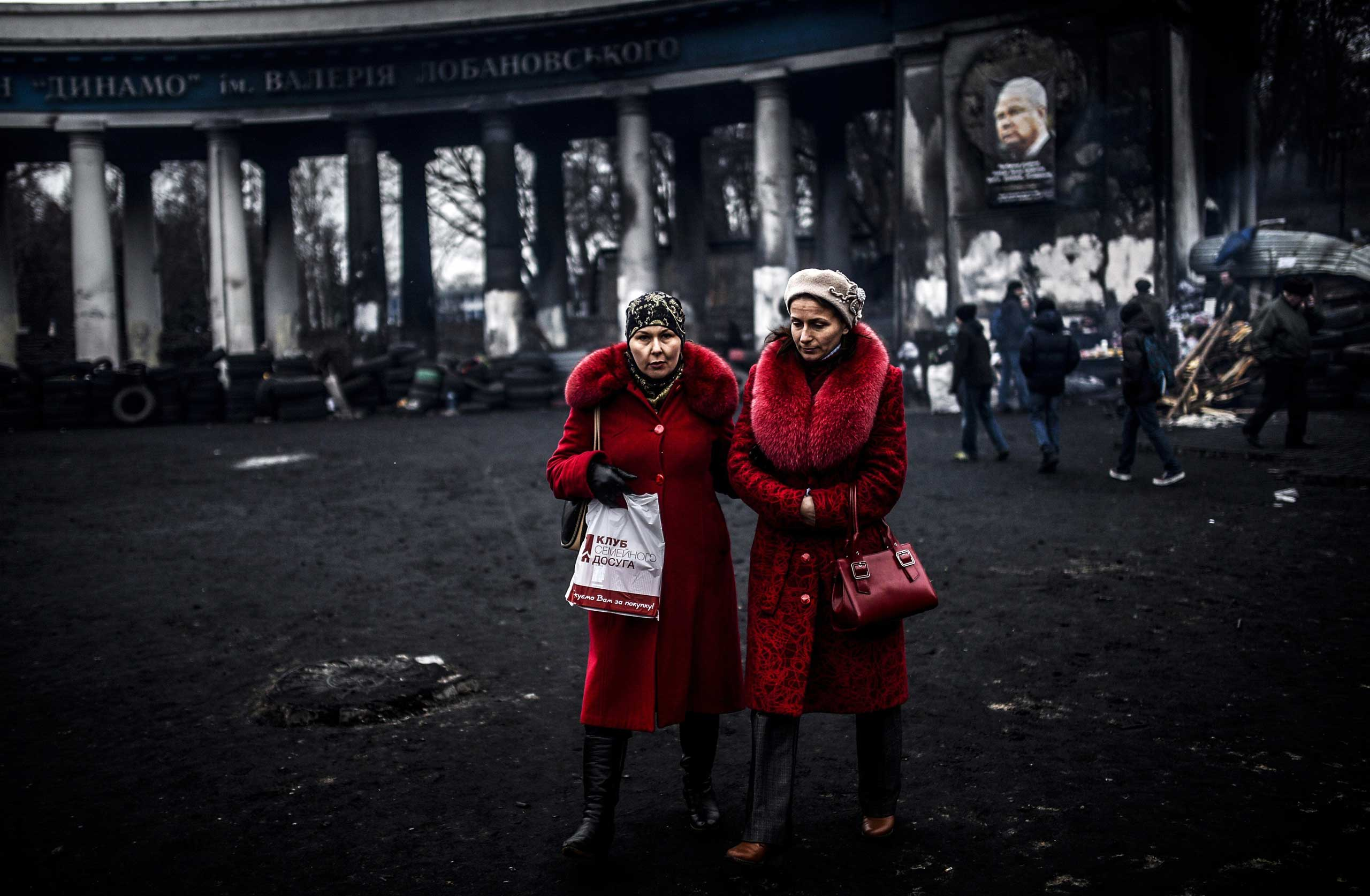 Women walk in front of the Dinamo Kiev's stadium on Feb. 25, 2014, in Kiev.