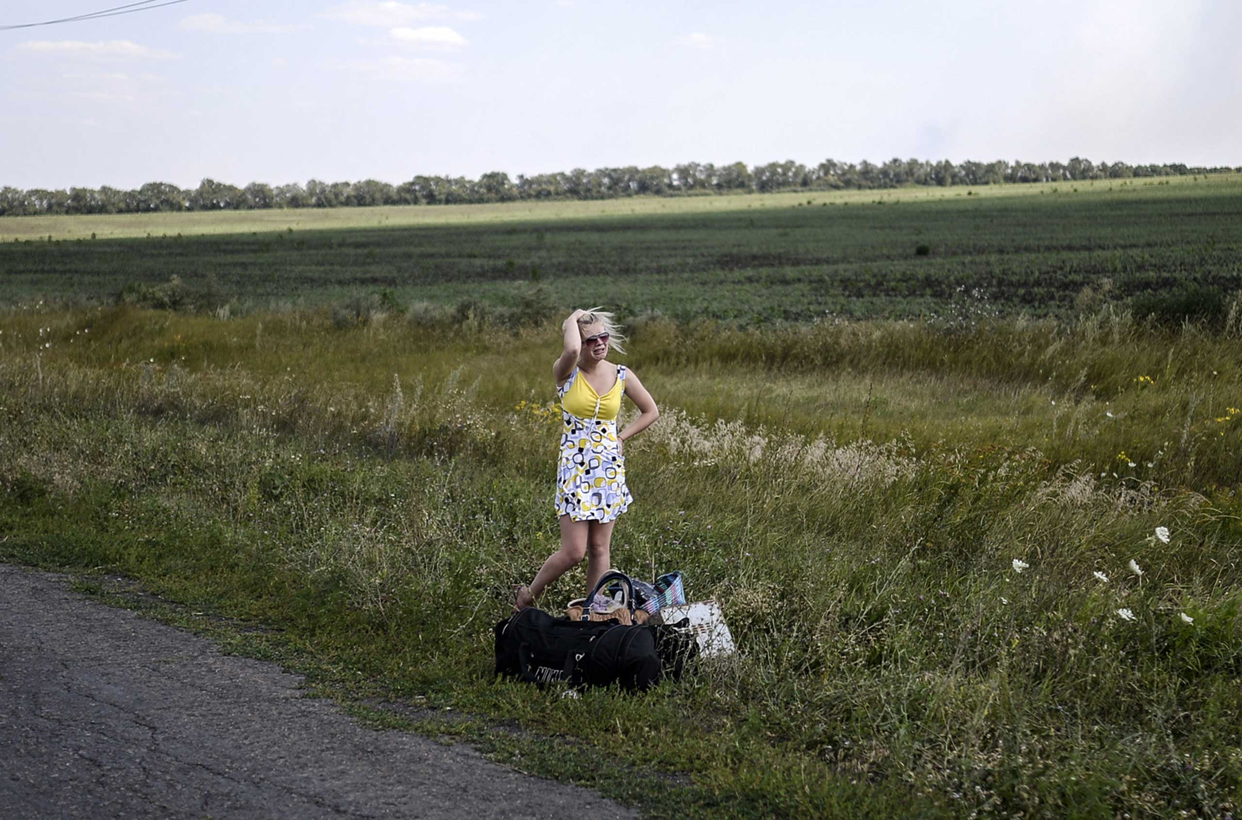 An Ukrainian girl cries as she stands on the road with her luggage after she left her home near the village of Hrabove (Grabovo), around 80km east of Donetsk, Ukraine, on Aug. 2, 2014.