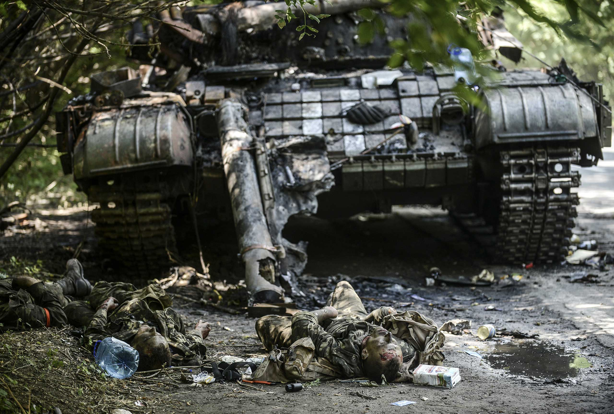 Bodies of crew members lie next to a destroyed Ukrainian tank in the northern outskirts of the city of Donetsk, Ukraine, on July 22, 2014.