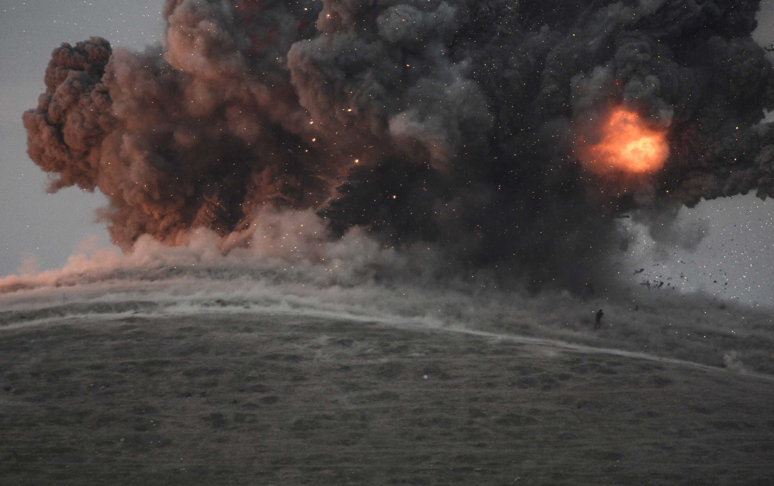 Militants of Islamic State (IS) are seen during an air strike on a hill near the Turkish border on Oct. 23, 2014.