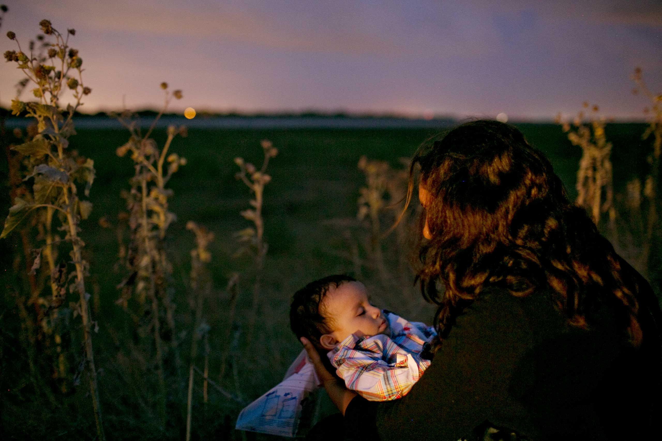 TIME LightBox: Documenting Immigration From Both Sides of the BorderA woman and her child from Central America are apprehended just after crossing the Rio Grande, Hidalgo, Texas, June 24, 2014.