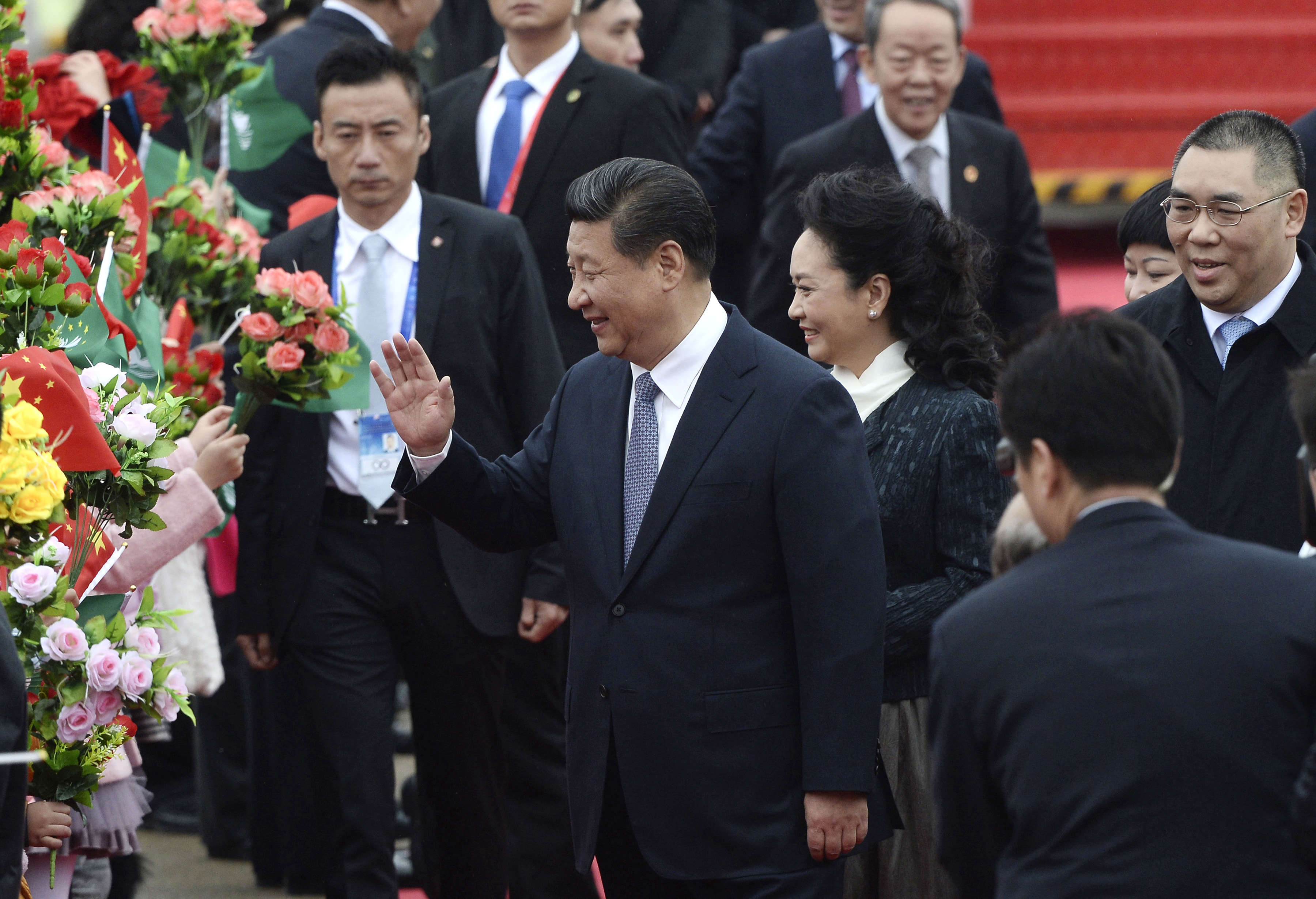 In this photo provided by China's Xinhua News Agency, Chinese President Xi Jinping, center, and his wife Peng Liyuan, center right,  wave as they arrive at the international airport in Macau on Dec. 19, 2014