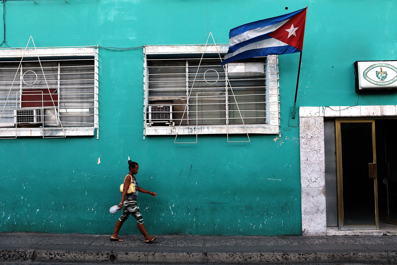 A woman walks under a Cuban flag on March 22, 2012 in Santiago de Cuba, Cuba.