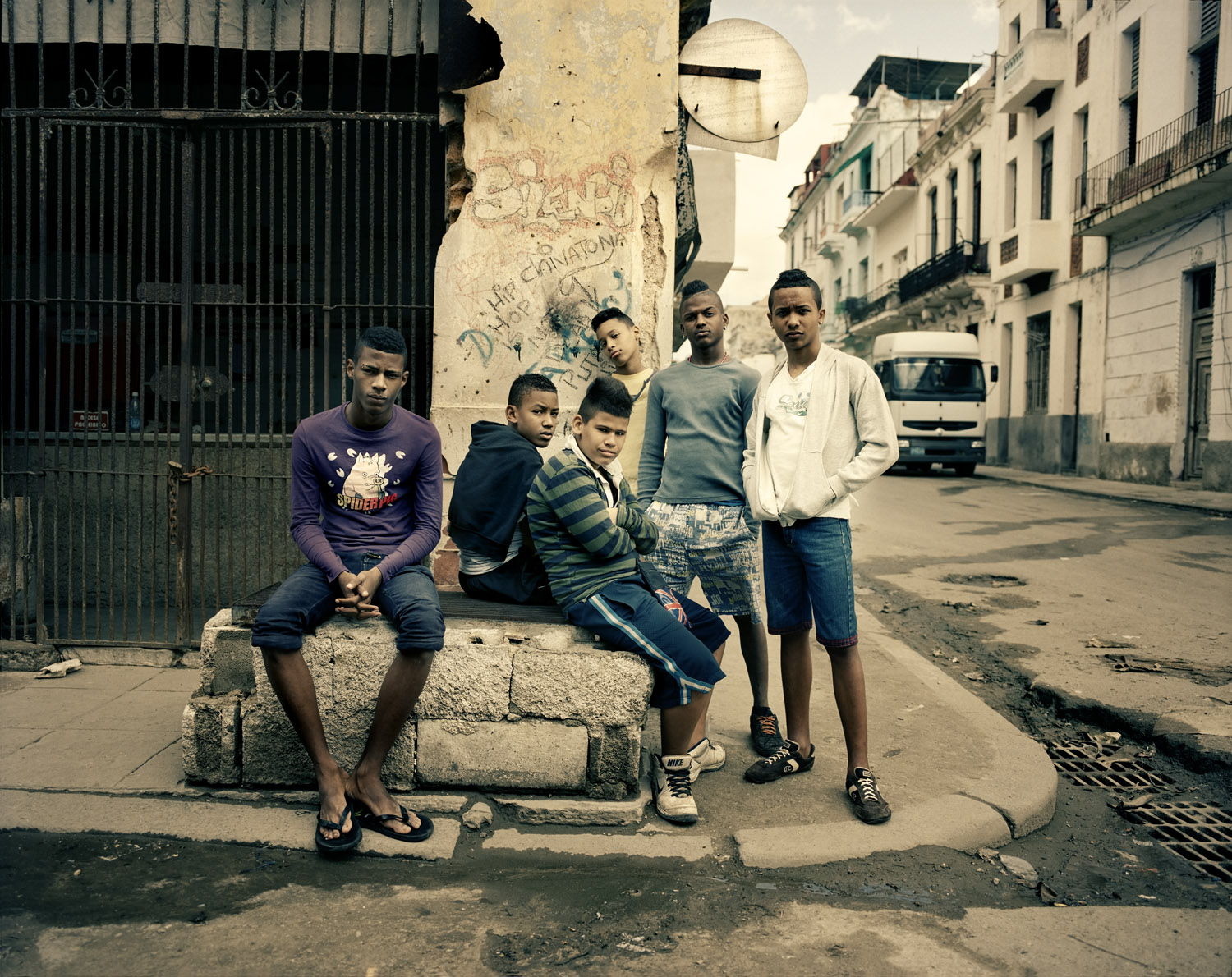 A group of youngsters in Central Havana sit on a street corner to discuss the latest news of the Spanish La Liga football league. Their hair is styled like their idols'—soccer stars and Reggaeton singers.