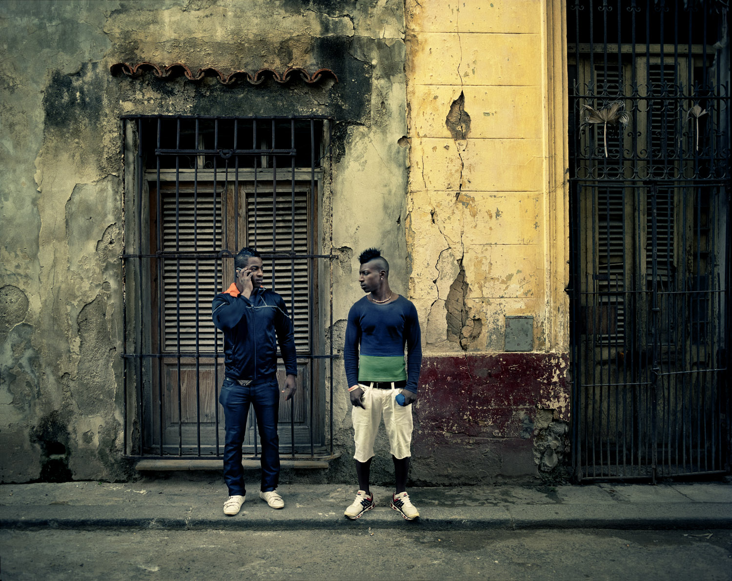 "Two young men wait to go out with a girl in Old Havana. ""We dress to impress her,"" they said, ""and we take pictures to our barber for him to know exactly what we want."""