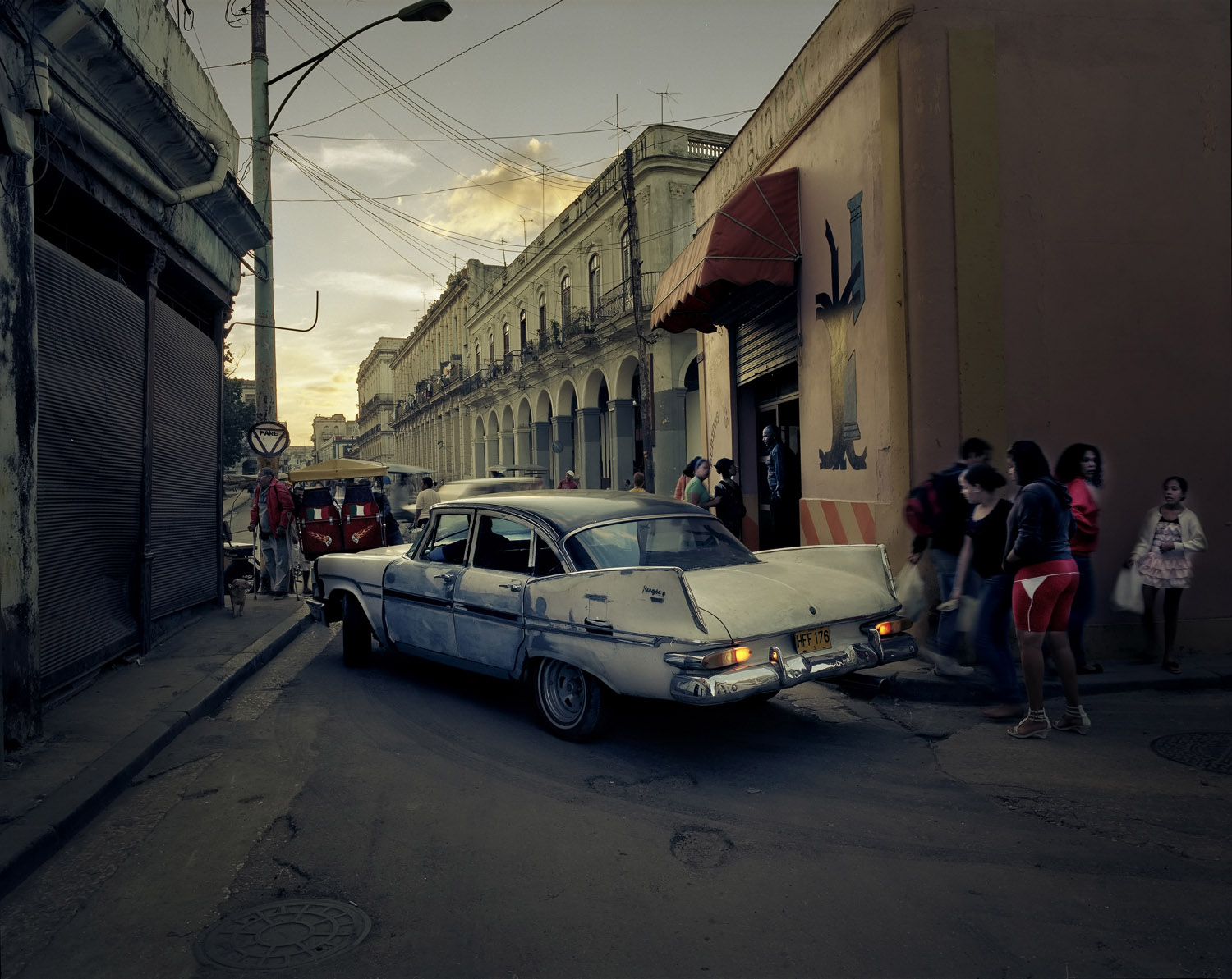 An aging car drives through Old Havana at dusk.