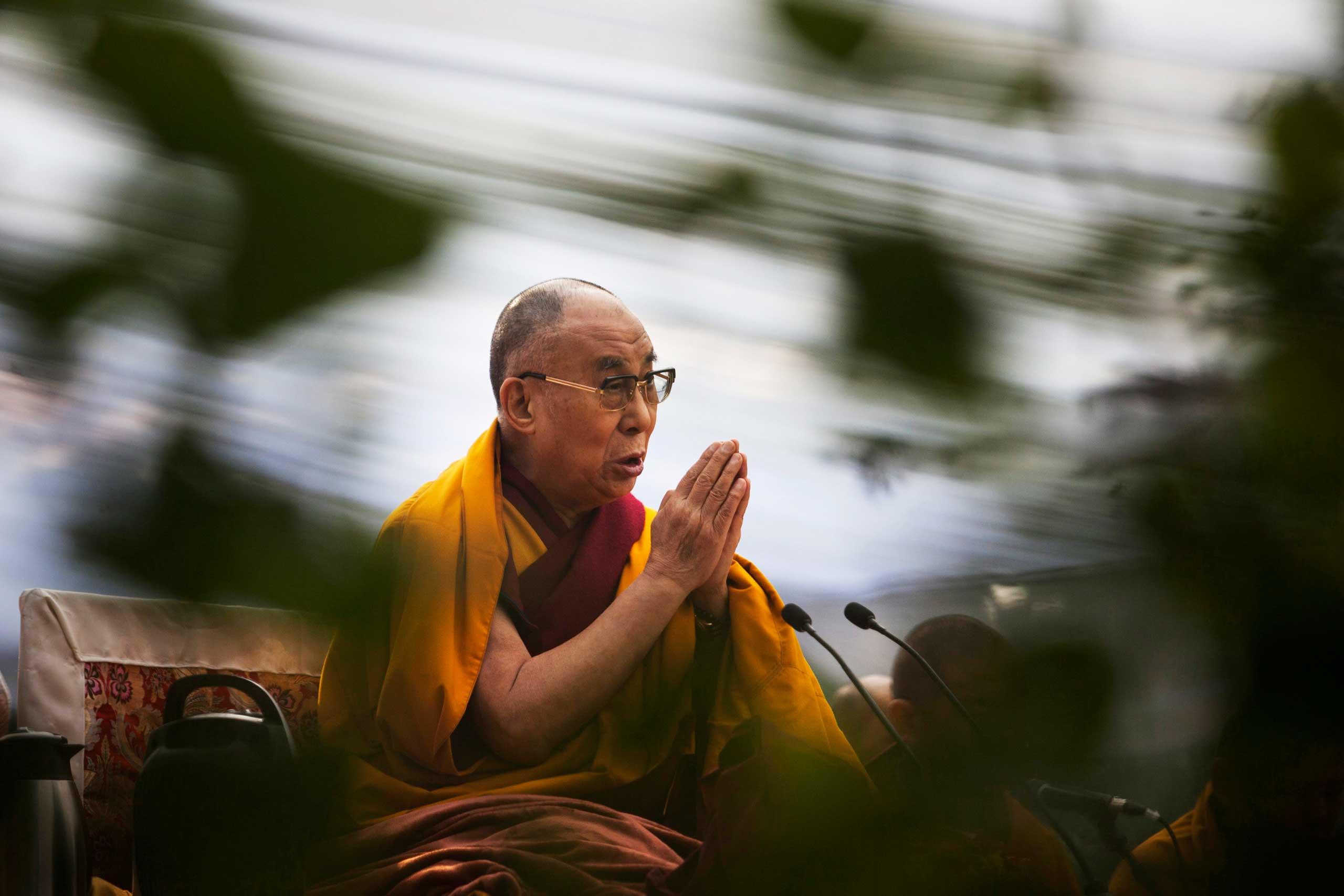 Tibetan spiritual leader the Dalai Lama prays during Ganden Ngachoe, the death anniversary of 14th Century Tibetan Saint-Scholar Lama Tsongkhapa, in New Delhi, India, Dec. 16, 2014.