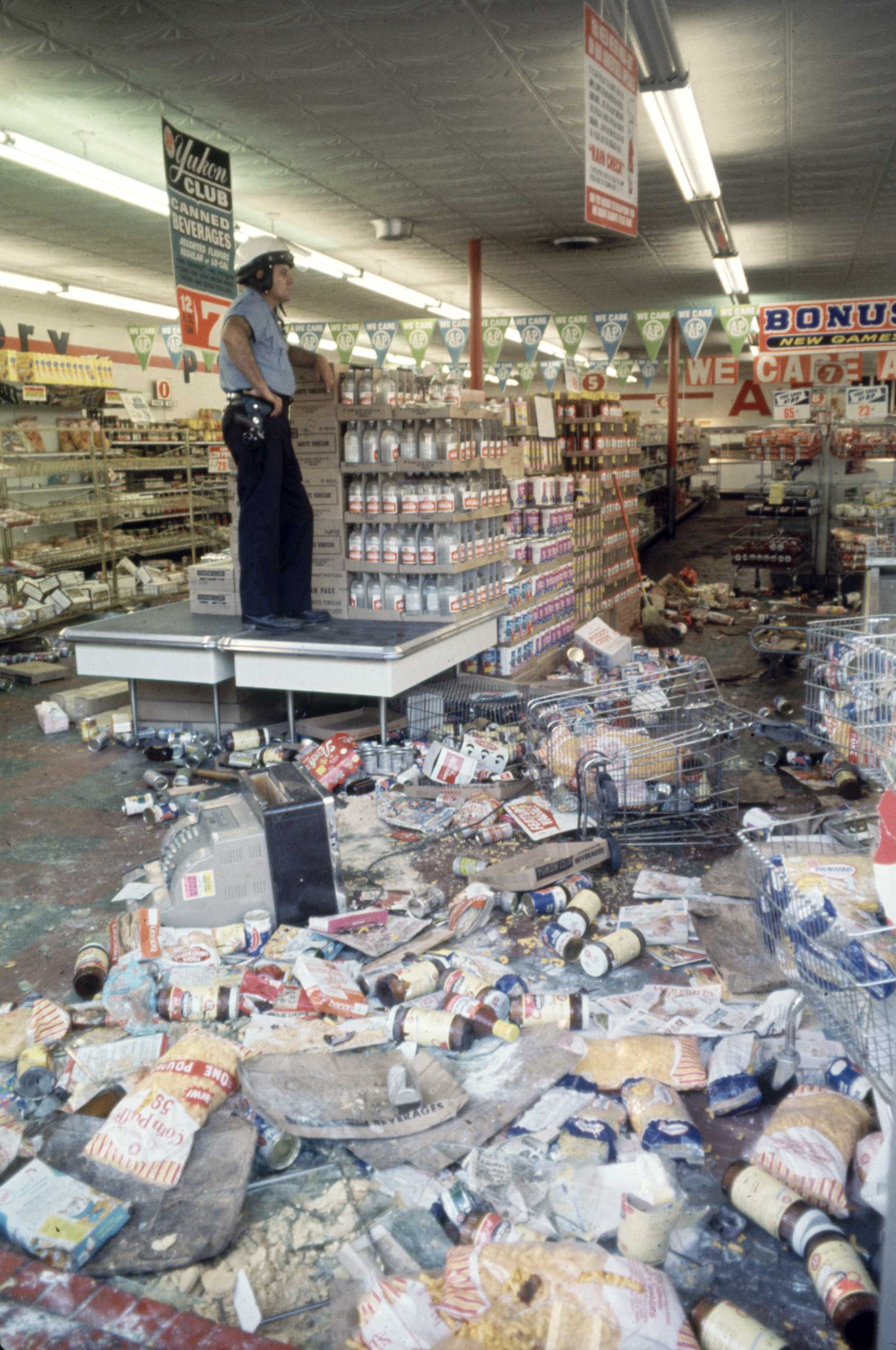 <b>Not published in LIFE.</b> Detroit, July 1967. A Detroit police officer stands guard over a grocery store looted during race riots.