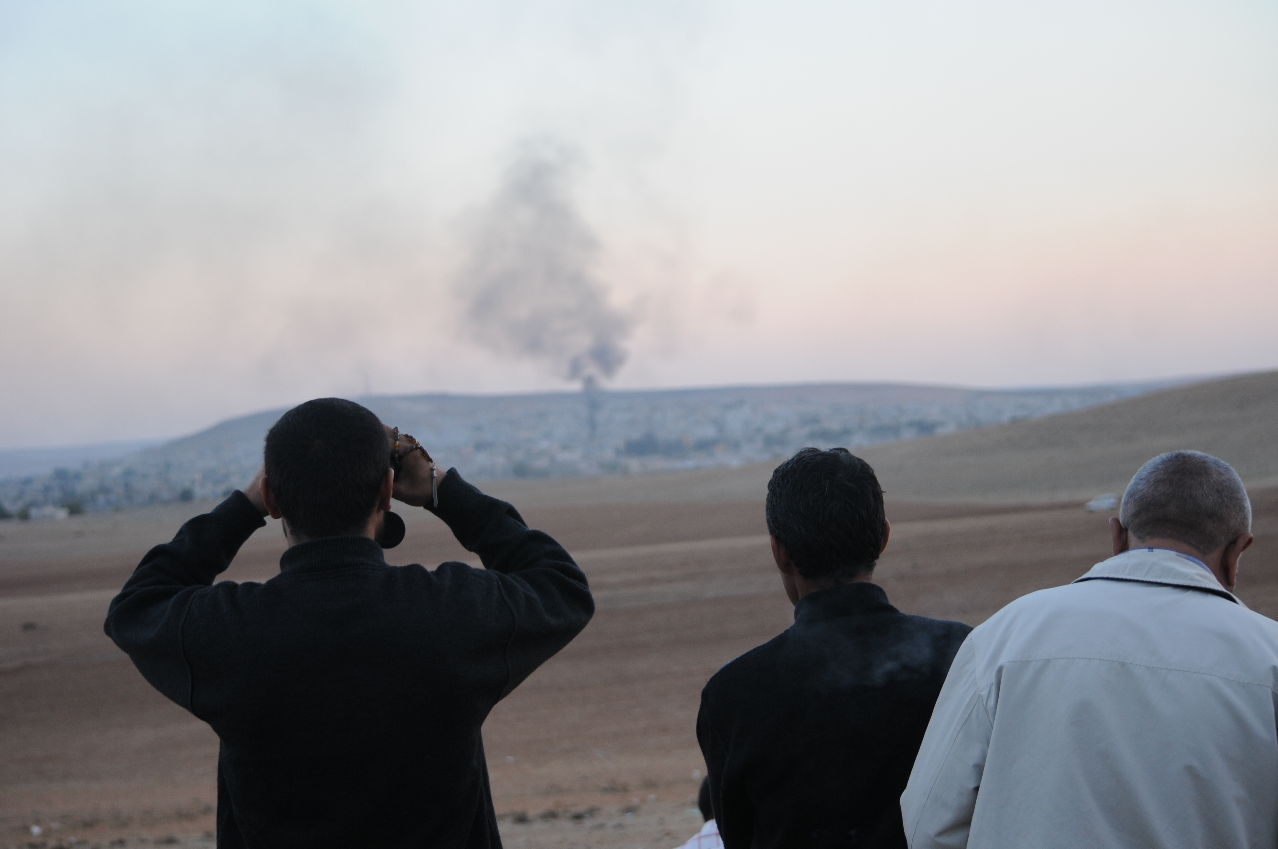 Groups of Kurdish men look at the siege of the Syrian town of Kobane from the Turkish border.
