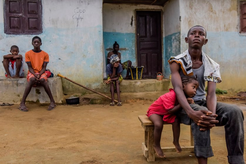Family of Isatu Sesay, 16, an Ebola victim, grieve as they wait for a burial team to collect Sesay's body, in Kissi Town, Sierra Leone.