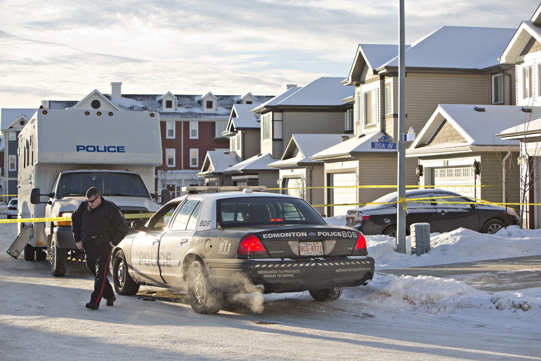 Police investigate the scene where multiple deaths occurred overnight in Edmonton, Alberta, Tuesday, Dec. 30, 2014.