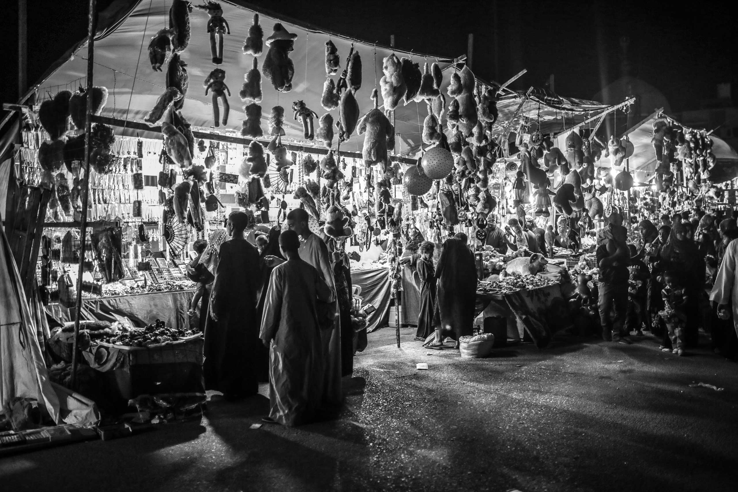 Attendees outside the Abul-Hassan Al-Shazly mosque shop for cheap merchandise during the weeklong celebration. Humaithara, Red Sea Governorate, Egypt. Sept. 30, 2014.