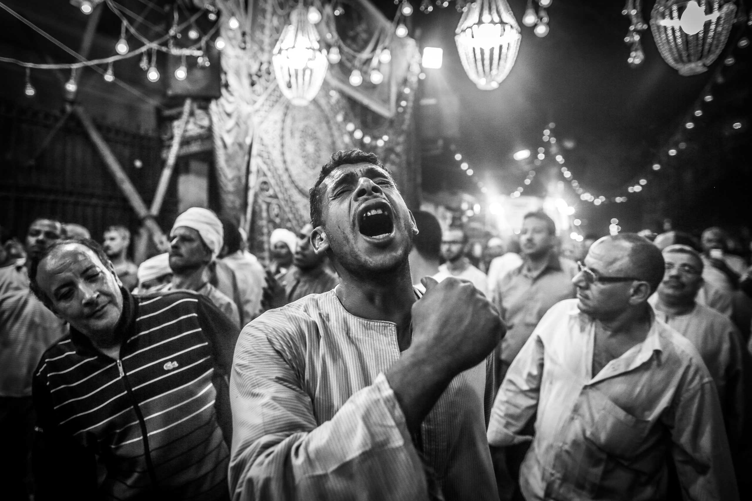Worshippers at a celebration at the Sayeda Zeinab mosque take part in a performance called Hadra, in which they whirl for long periods. Downtown Cairo, Egypt. May 20, 2014.
