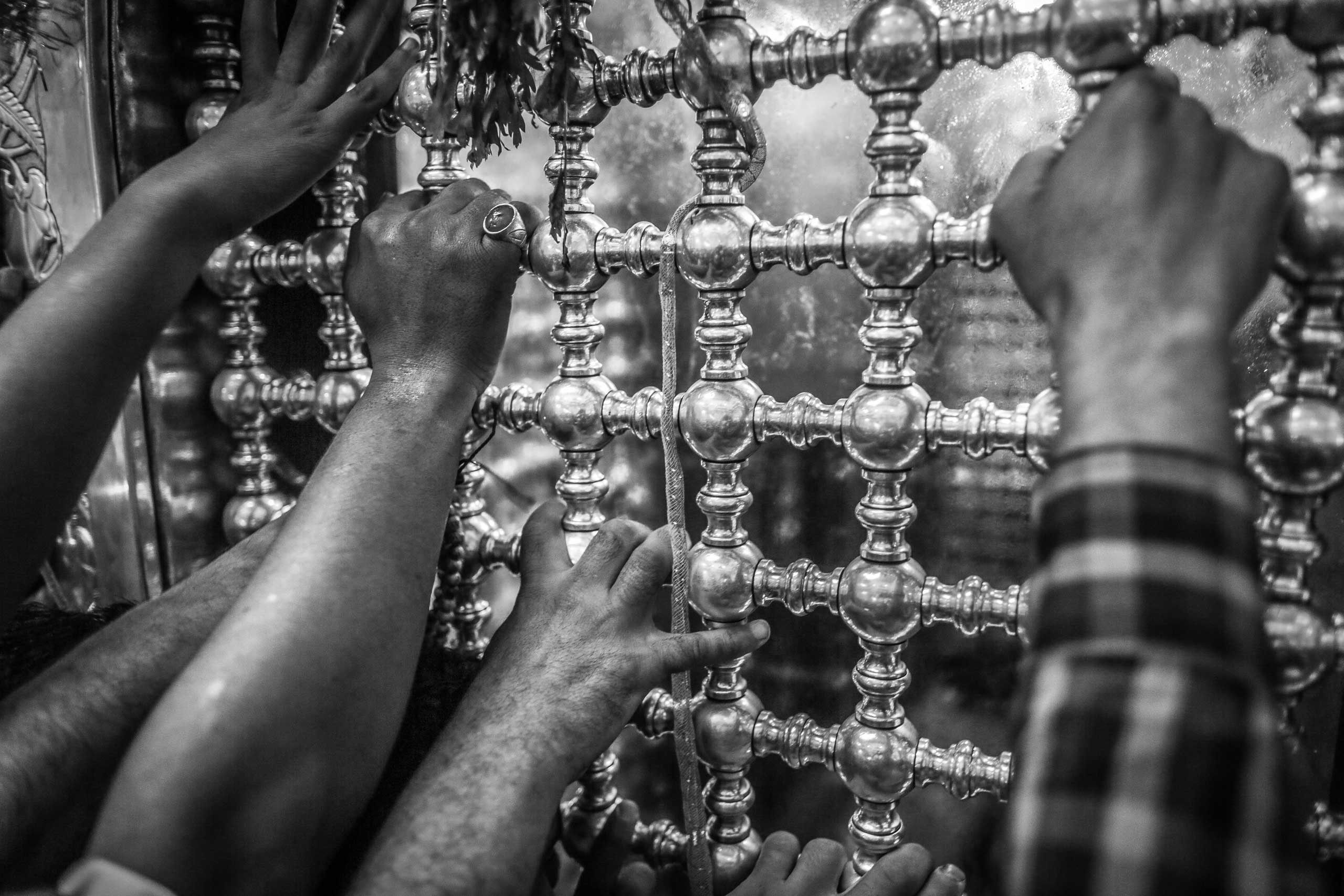Worshippers surround the shrine of Sayeda Zeinab, granddaughter of the Prophet Muhammad, during the celebration of her birthday. Holding the shrine becomes the main goal for the thousands of attendees who then recite prayers or seek blessings through it. Downtown Cairo, Egypt. May 20, 2014.