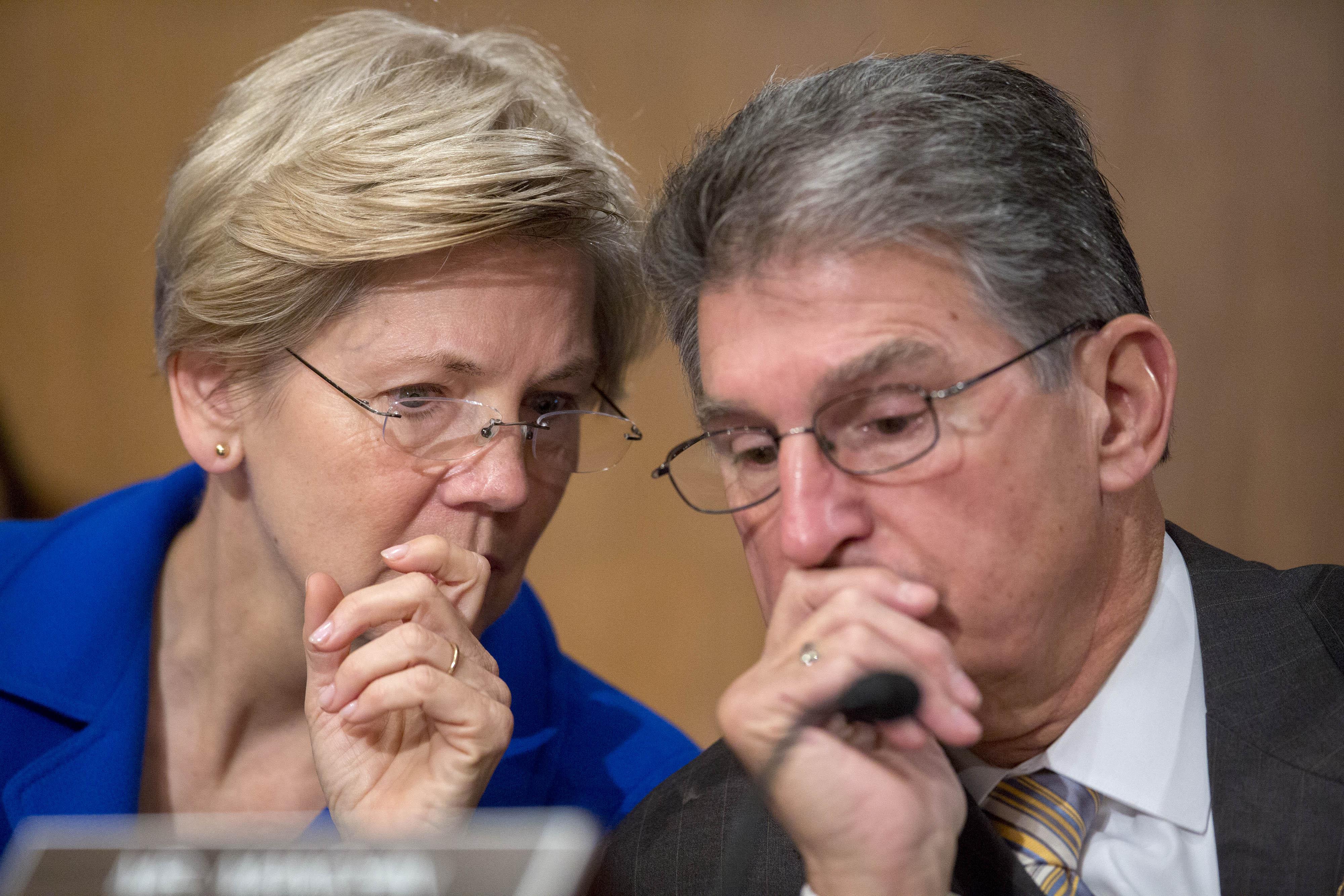 From Left: Senator Elizabeth Warren a Democrat from Massachusetts speaks with Senator Joe Manchin a Democrat from West Virginia during a Senate Banking Subcommittee in Washington, D.C. on Nov. 21, 2014.