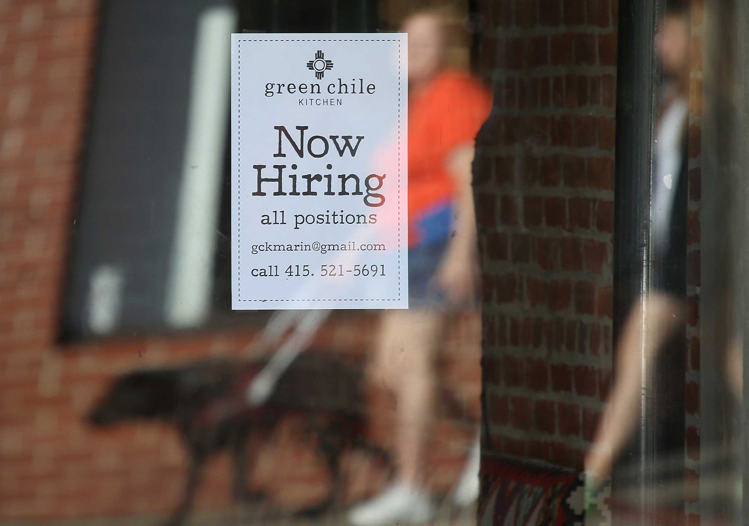 Pedestrians walk by a now hiring sign posted in the window of a business on Nov. 7, 2014 in San Rafael, Calif.