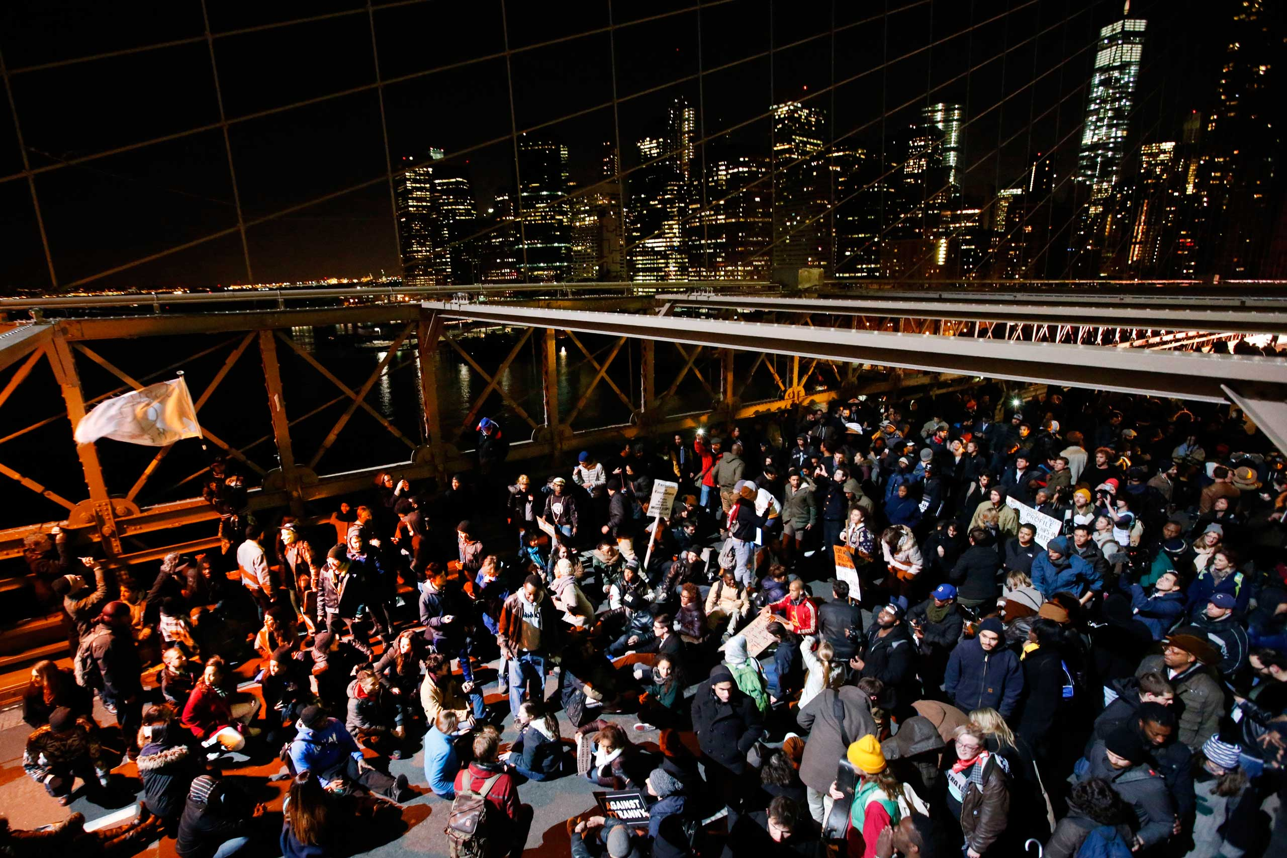 A group of protesters rally against a grand jury's decision not to indict the police officer involved in the death of Eric Garner occupy the eastbound traffic lanes of the Brooklyn Bridge in  New York City in the early morning hours of Dec. 4, 2014.