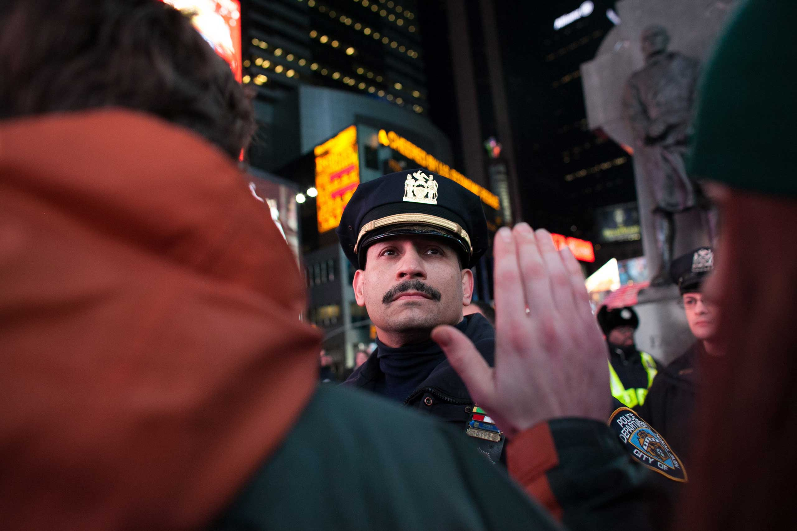 Protesters raise their arms and chant at police officers in Times Square in New York City on Dec. 3, 2014.