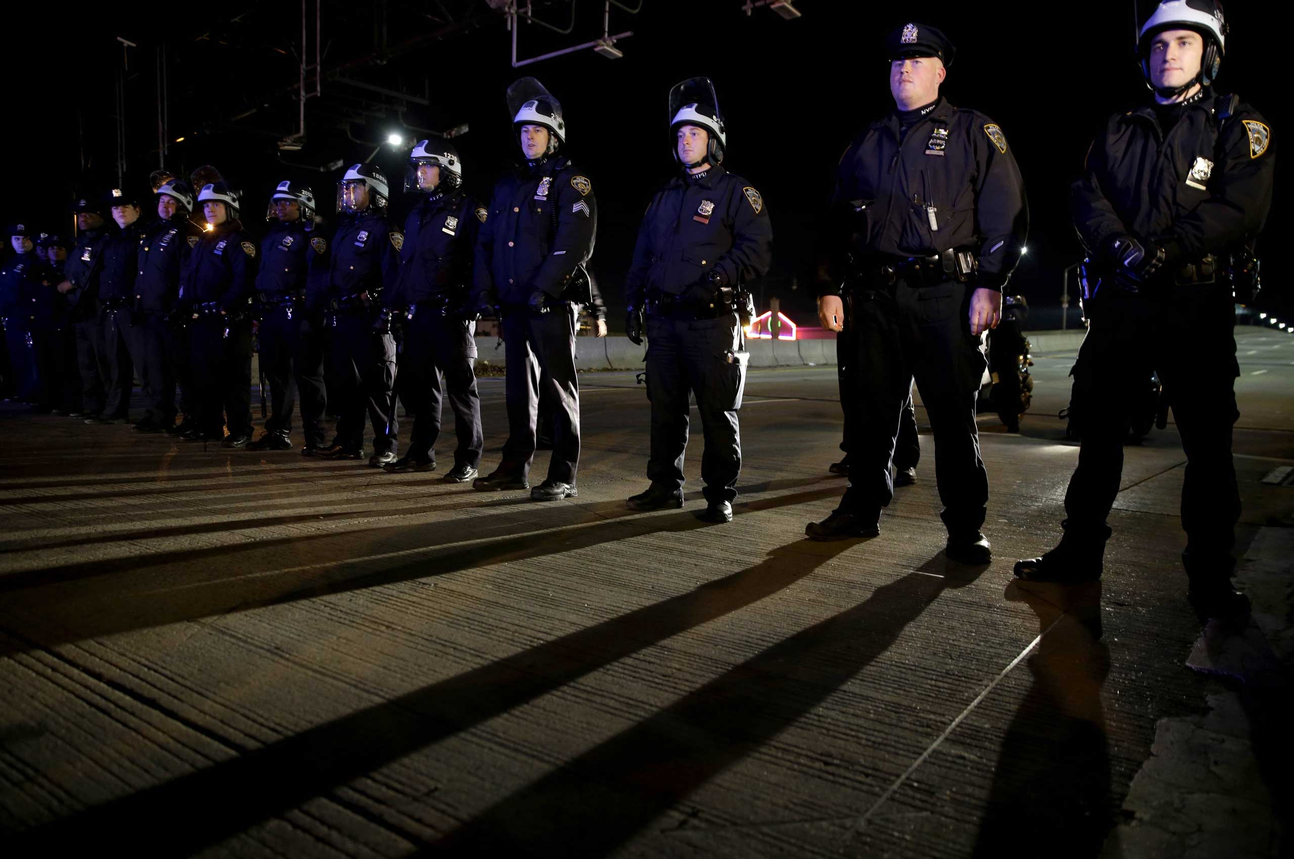 Police officers block protesters from marching up a highway entrance ramp near Times Square in New York City on Dec. 3, 2014.