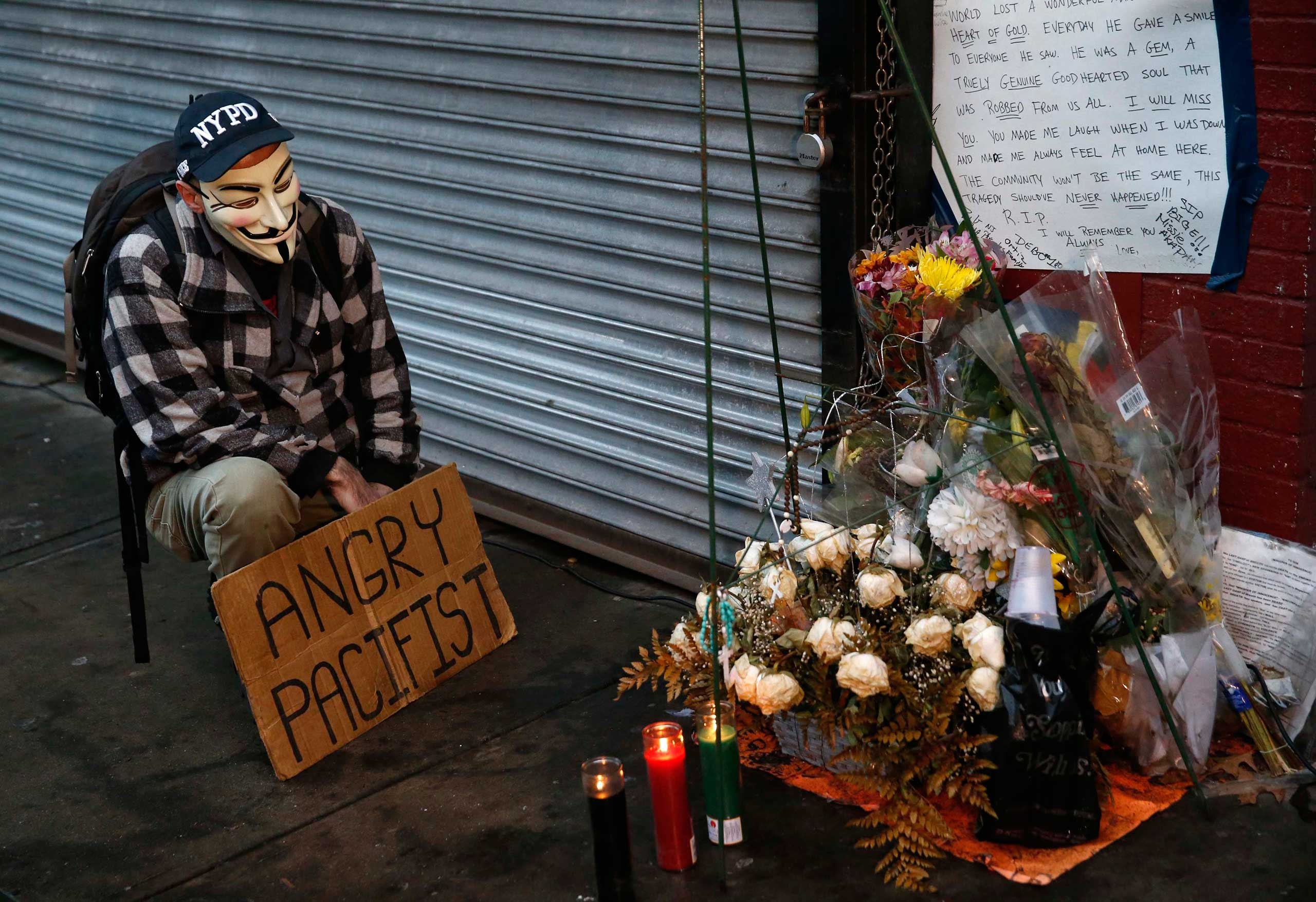 A demonstrator stands next to a makeshift memorial where Eric Garner died during an arrest in July in the Staten Island borough of New York City on Dec. 3, 2014.
