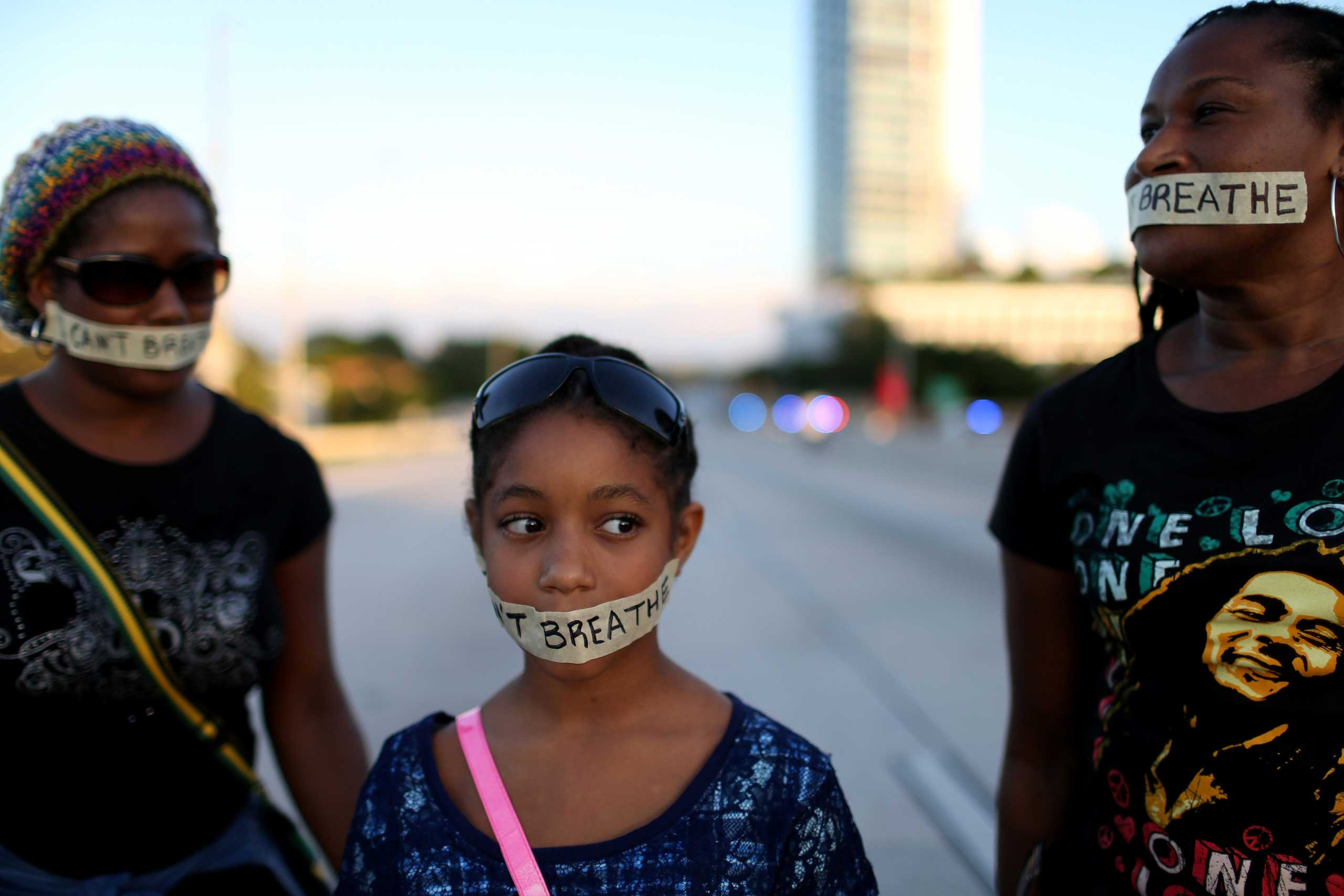 Demonstrators stand with tape reading,   I Can't Breathe , as they march along Interstate 195 after police shut the road down on Dec. 7, 2014 in Miami.