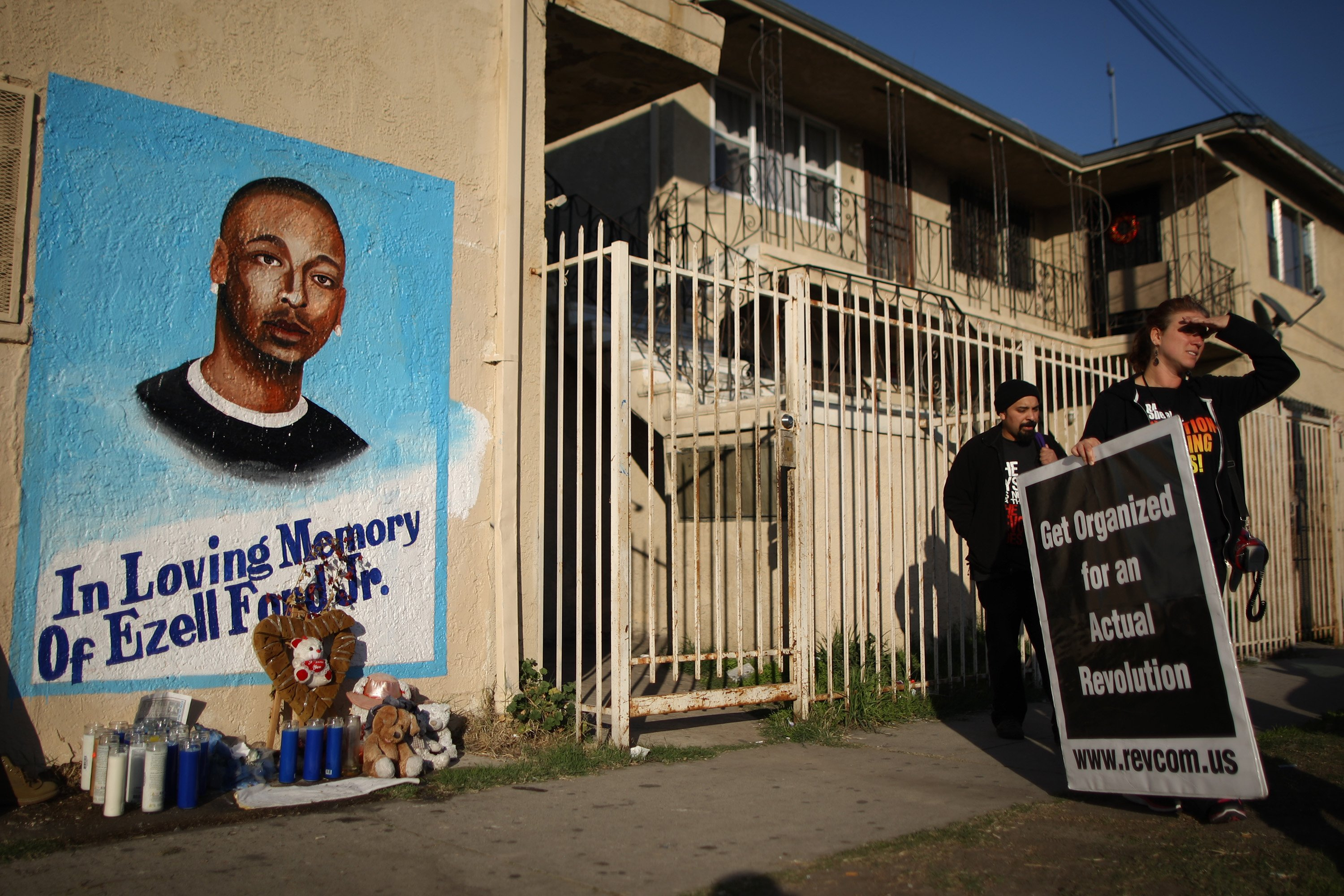Activists look at a mural of Ezell Ford, a 25-year-old mentally ill black man at the site where he was shot and killed by two LAPD officers in August on Dec. 29, 2014 in Los Angeles.