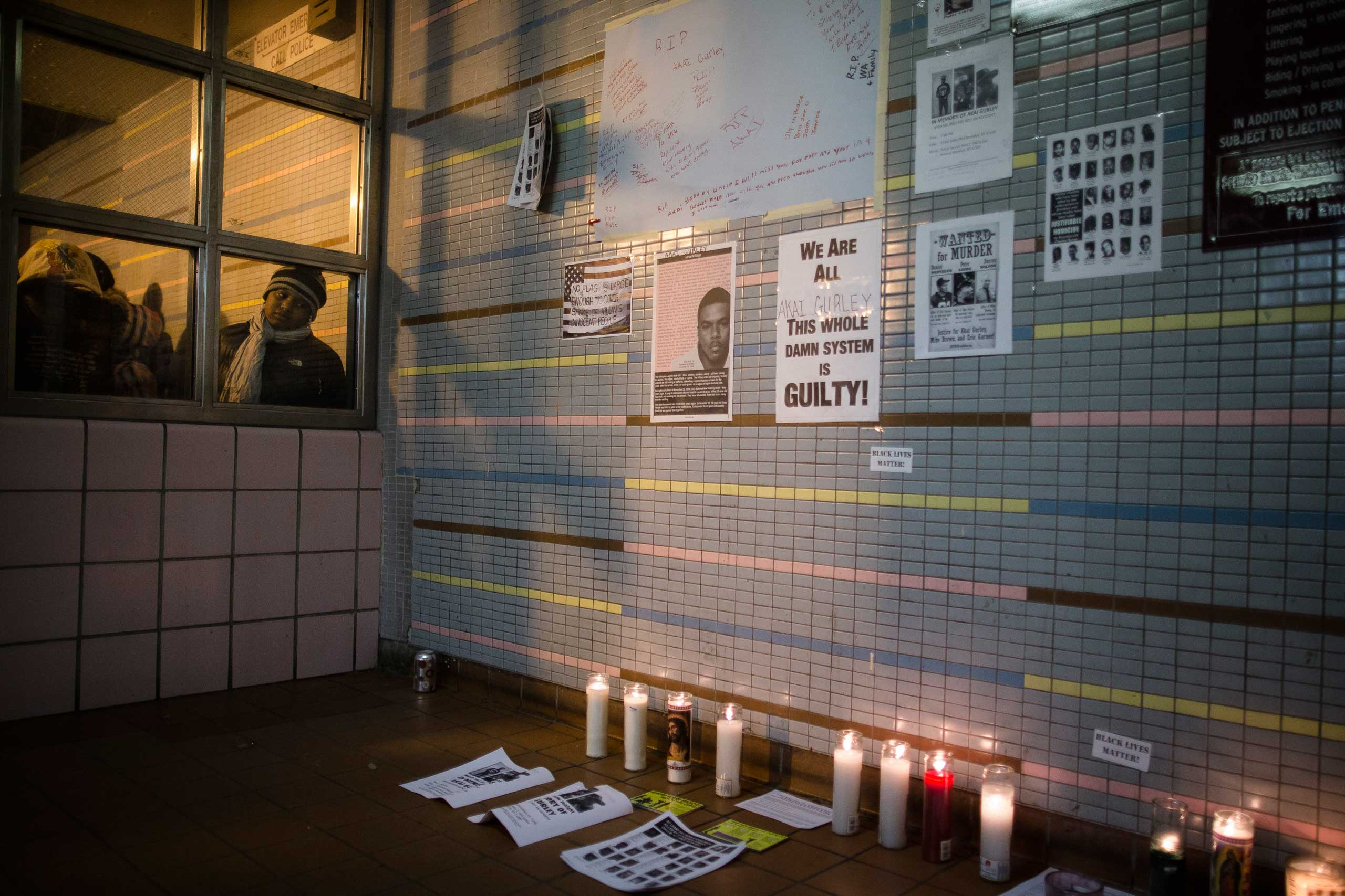 A demonstrator looks on a memorial to Akai Gurley who was shot to death by rookie NYPD officer Peter Liang at the Louis Pink Houses public housing complex, Nov. 22, 2014, in the Brooklyn borough of New York.