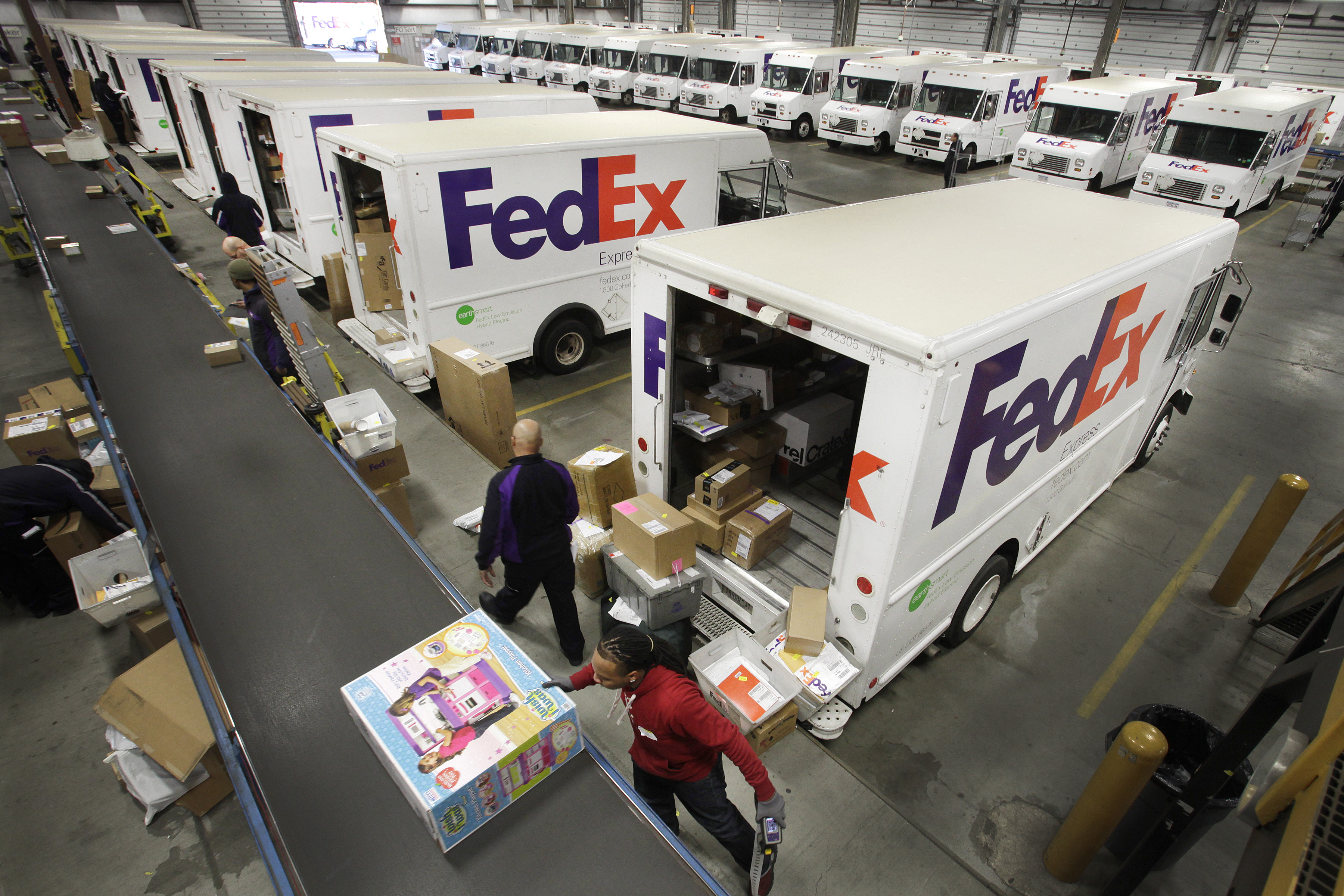 FedEx employees fill their trucks for deliveries at a FedEx sorting facility in the Bronx, New York on Dec. 15, 2014.