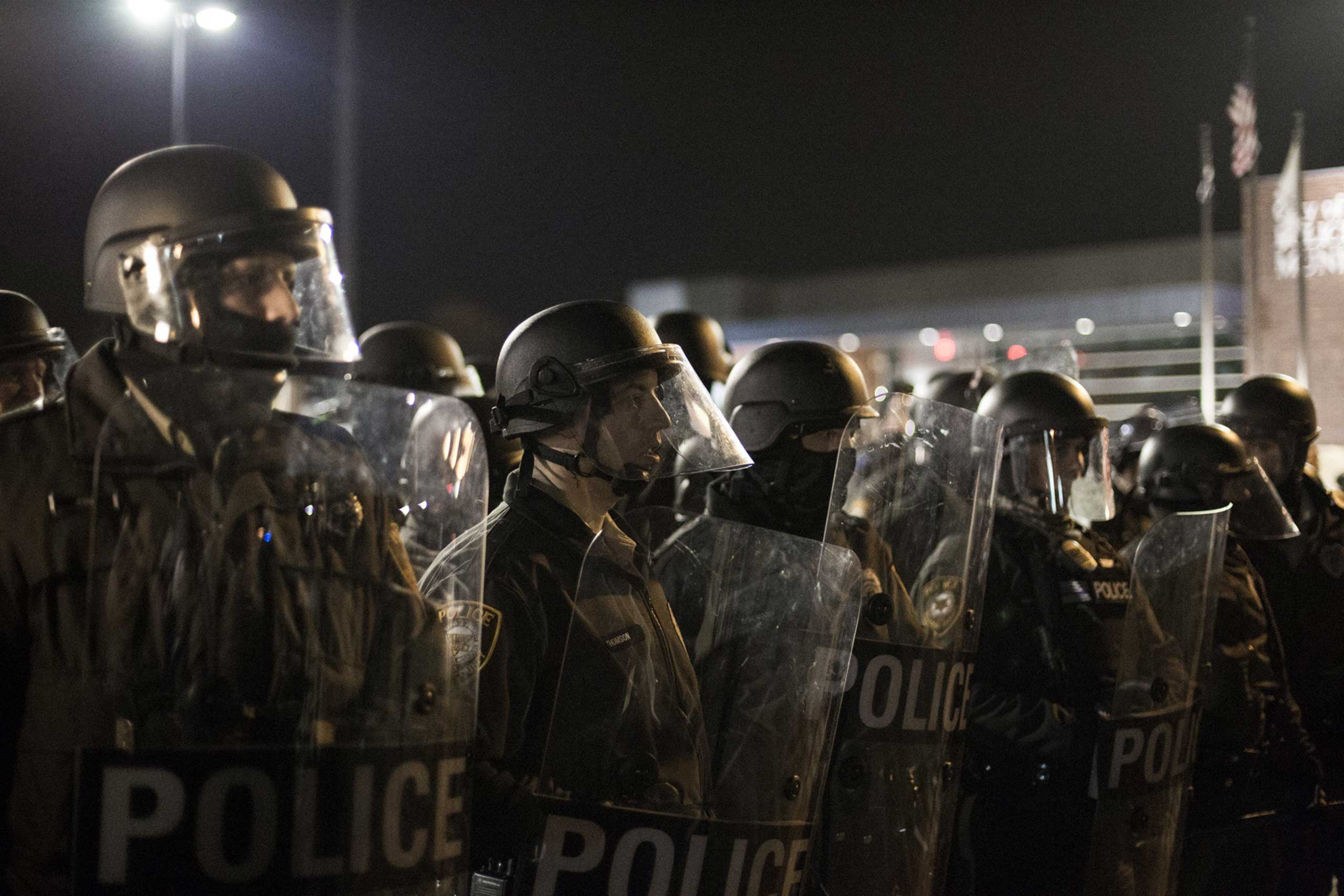 Police in riot gear stand in line opposing protesters in Ferguson, Mo. on Nov. 28, 2014.
