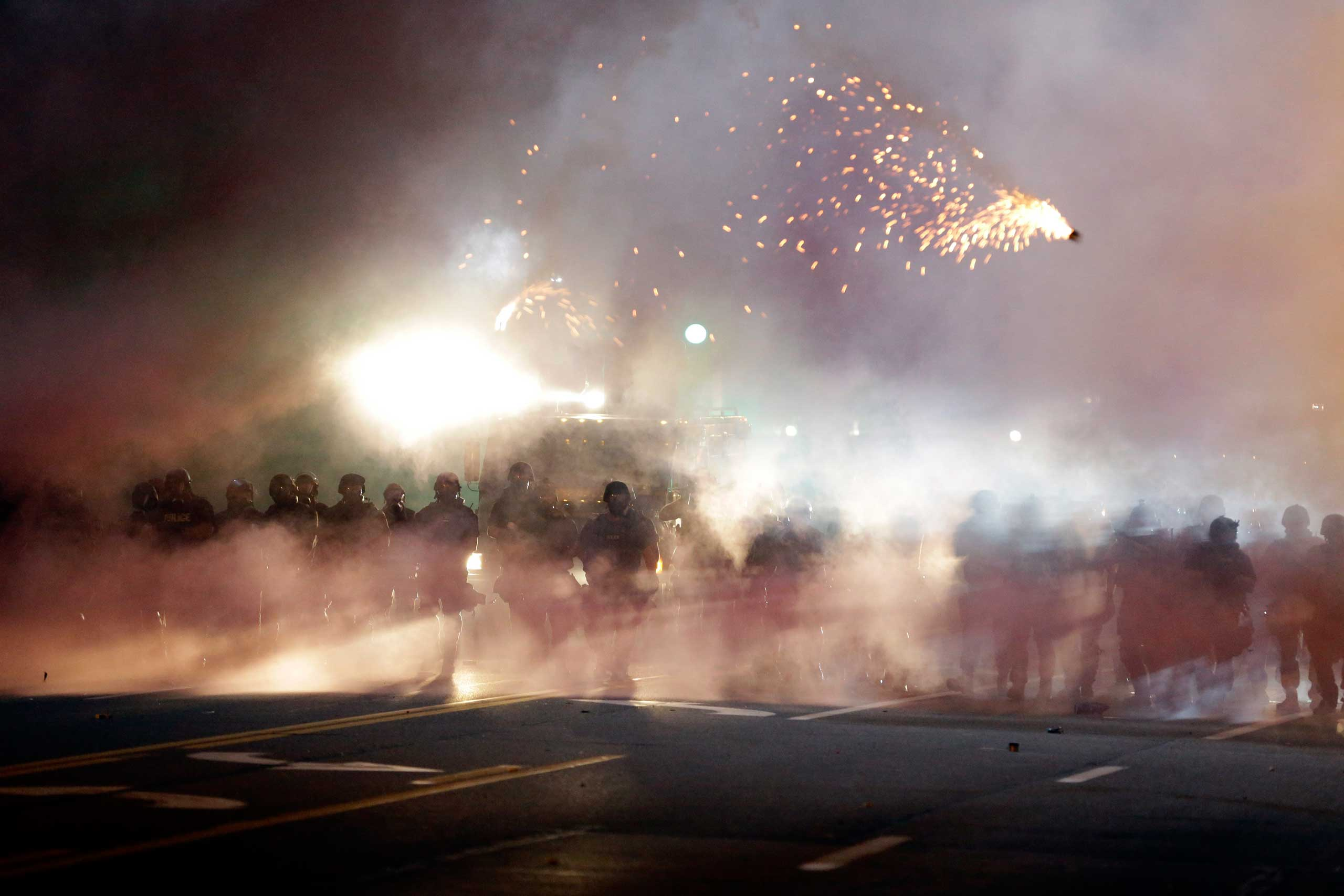 An explosive device deployed by police flies in the air as police and protesters clash after tear gas was thrown on Aug. 13, 2014, in Ferguson, Mo.