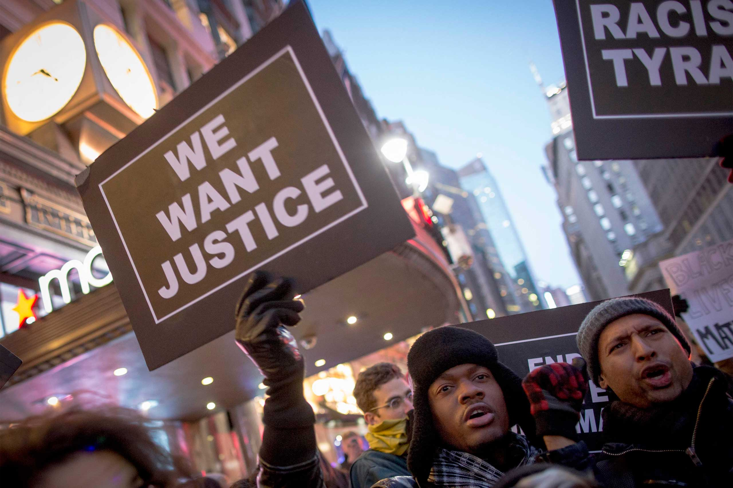 A protester holds up a sign while demonstrating against the grand jury decision in the case against Darren Wilson in Ferguson, outside of Macy's in New York City on Nov. 28, 2014.