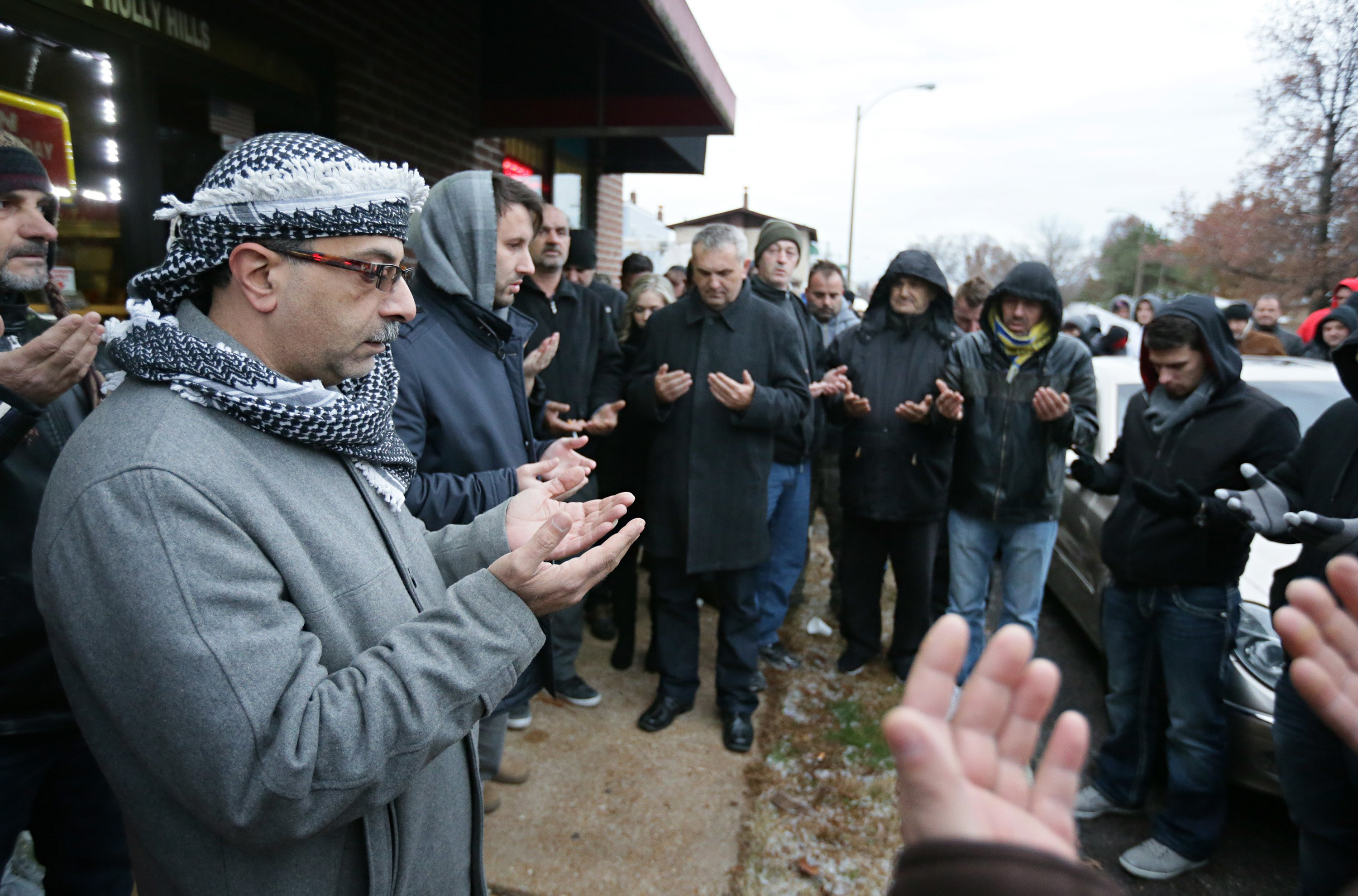 Zuhdi Masri, left, prays for murder victim Zemir Begic with a group of other Bosnians gathered on Holly Hills Avenue in St. Louis on Dec. 1, 2014.