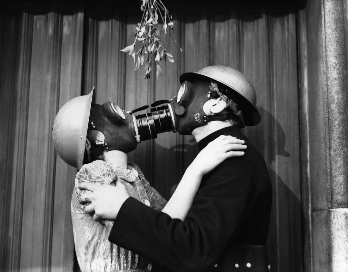 A couple kissing under the mistletoe, wearing gas masks, in 1940