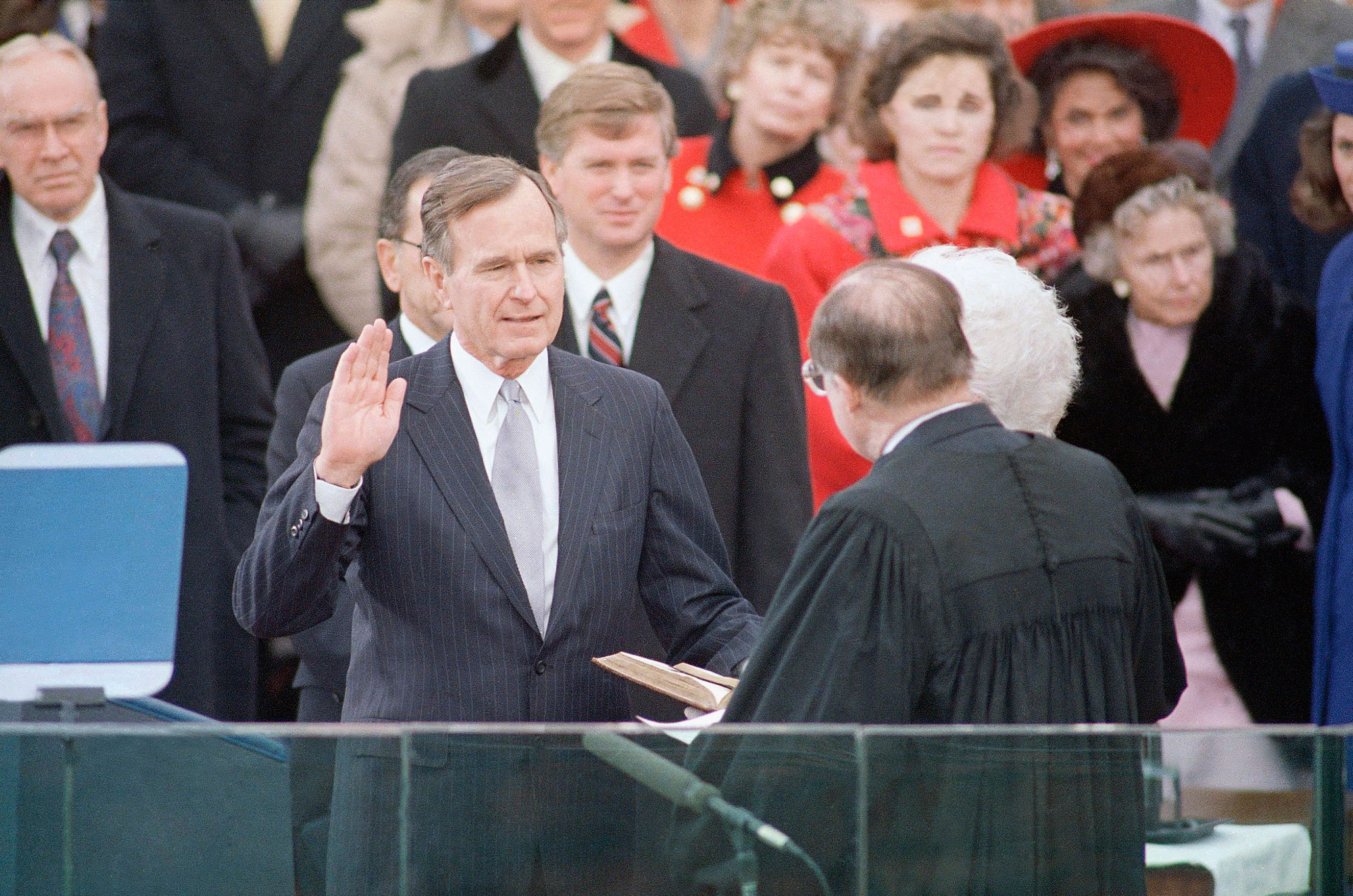 President George H. W. Bush raises his hand as he takes the oath of office as President of the United States outside the Capitol on Jan. 20, 1989, Washington, D.C.