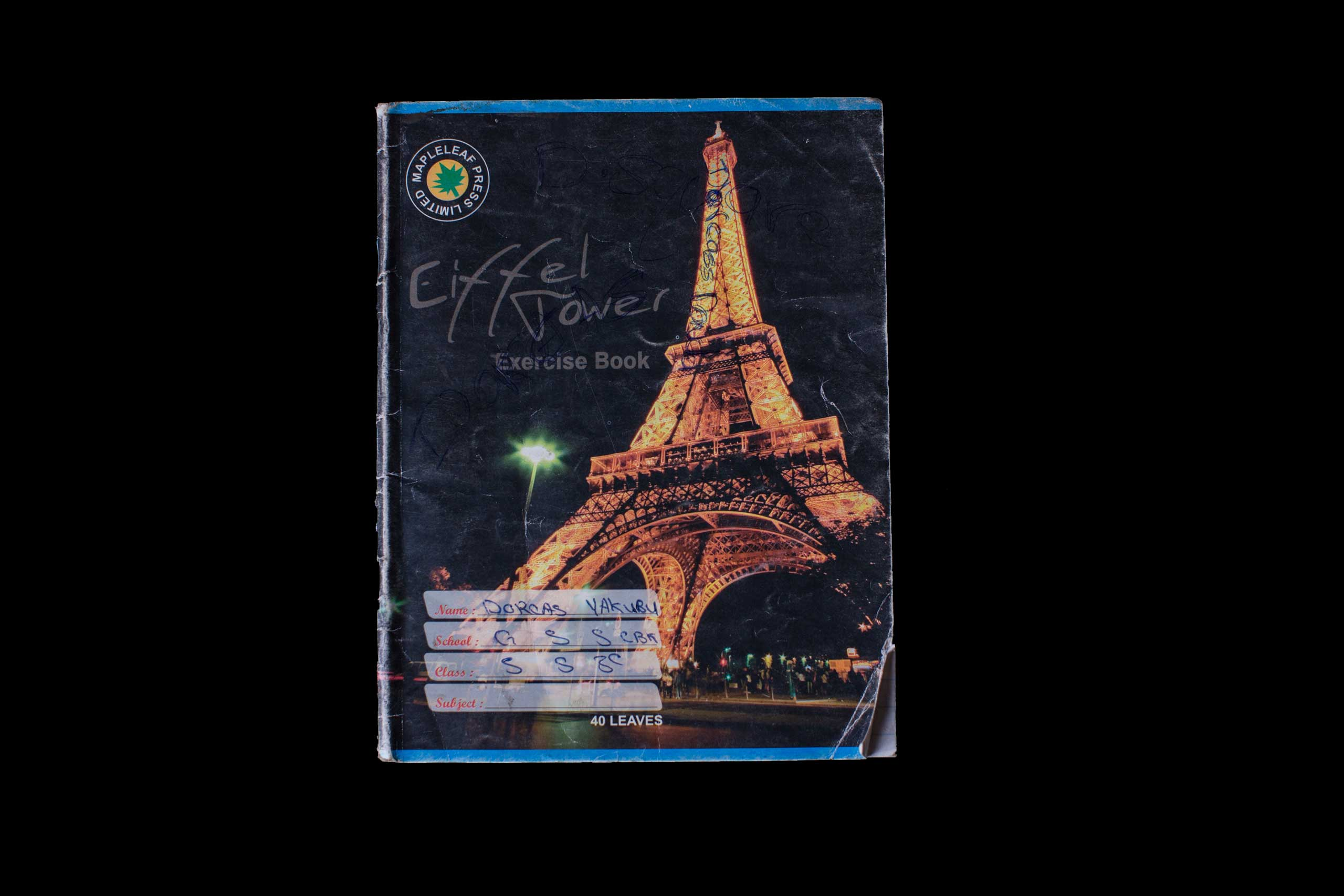 Nigerian schoolgirl notebook. Dorcas Yakubu is 16 years old. Her parents describe her as  shy girl who loved eating tuwo (a local dish). The cover of her notebook has the Eiffel Tower on it. Photo taken, Abuja, Nigeria, May 22, 2014.