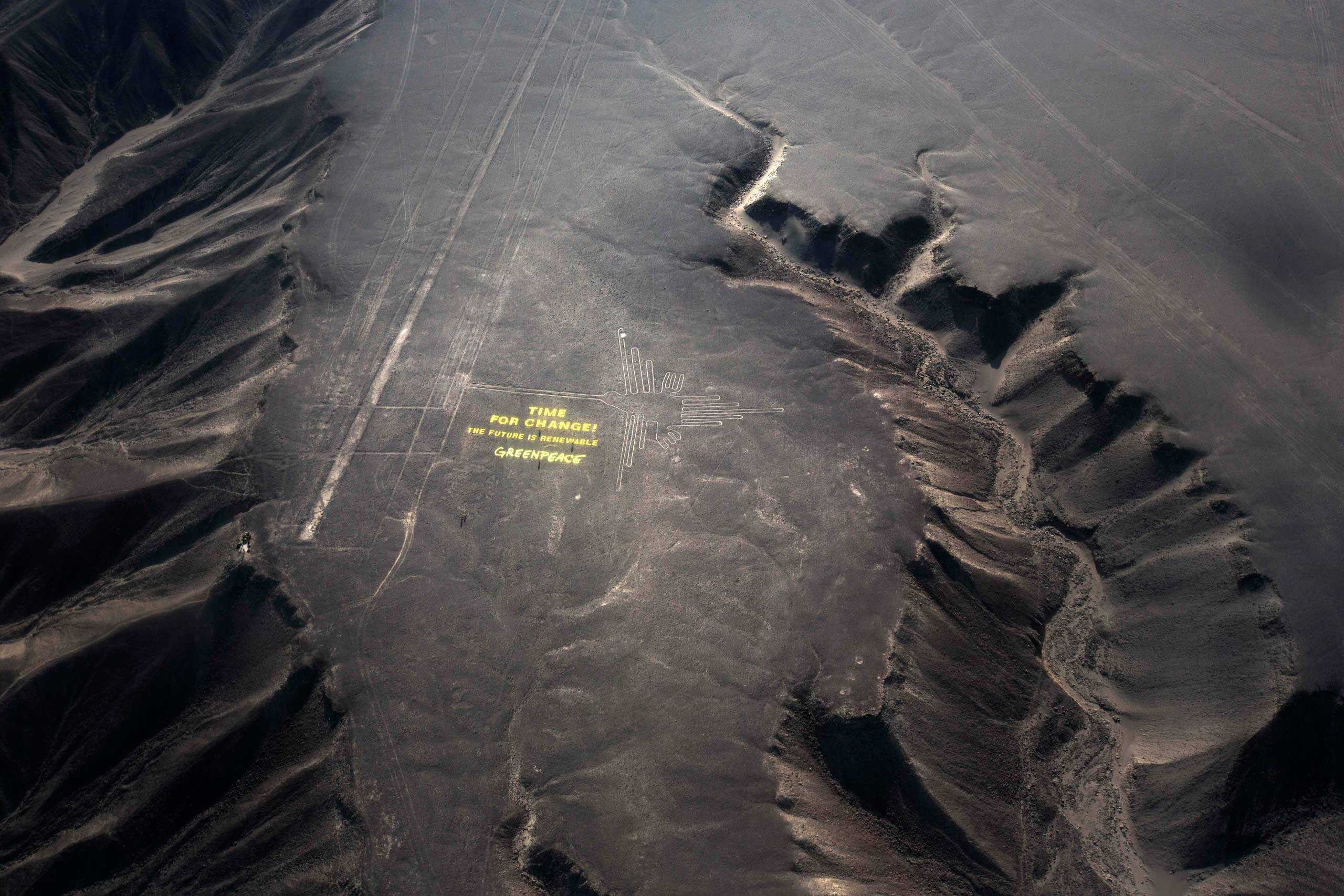 Greenpeace activists stand next to massive letters delivering the message  Time for Change: The Future is Renewable,  next to the hummingbird geoglyph in Nazca in Peru,, Dec. 8, 2014.