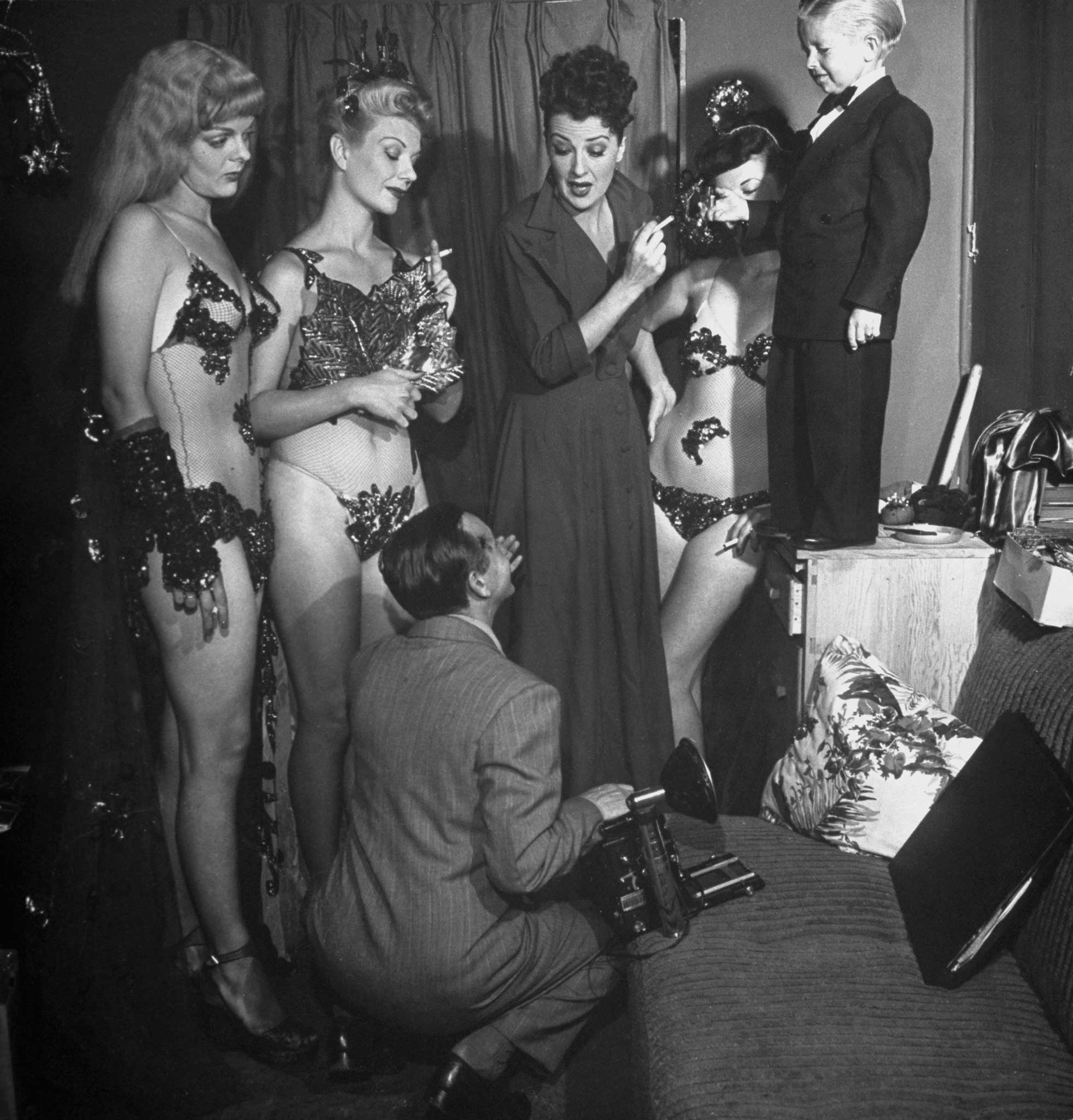 """<b>Not published in LIFE.</b> Gypsy Rose Lee and some of the dancers in her show pose for publicity pictures with the carnival's """"midget,"""" K. O. Erickson."""