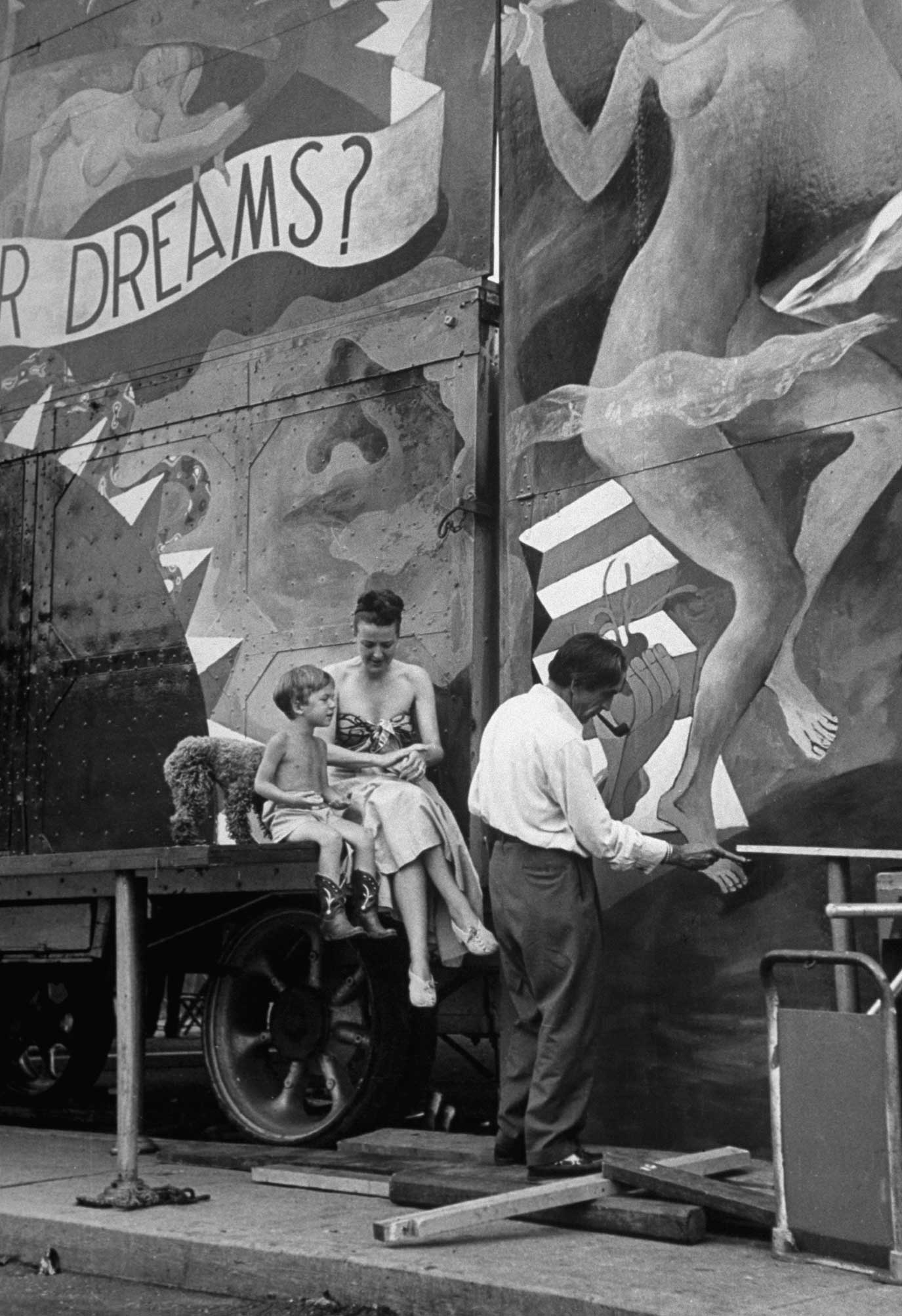 """<b>Caption from LIFE.</b> """"Gypsy's husband Julio . . . paints the entrance while Gypsy and son watch. His attraction [in the carnival] is called Dream Show."""""""