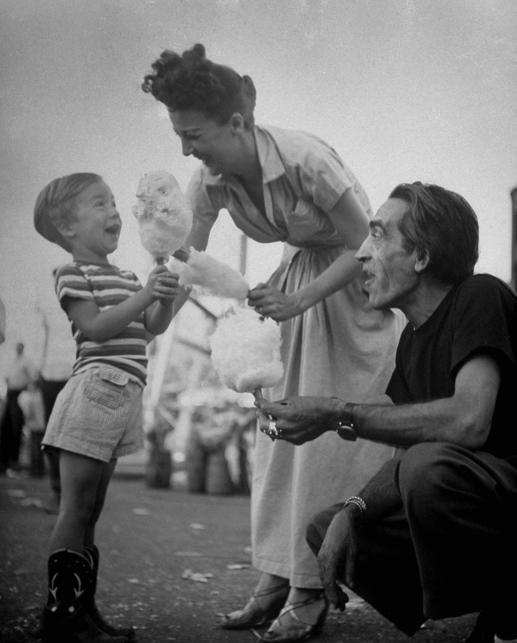 <b>Not published in LIFE.</b> Gypsy Rose Lee gives her son, Erik, cotton candy while her husband Julio De Diego watches, 1949.