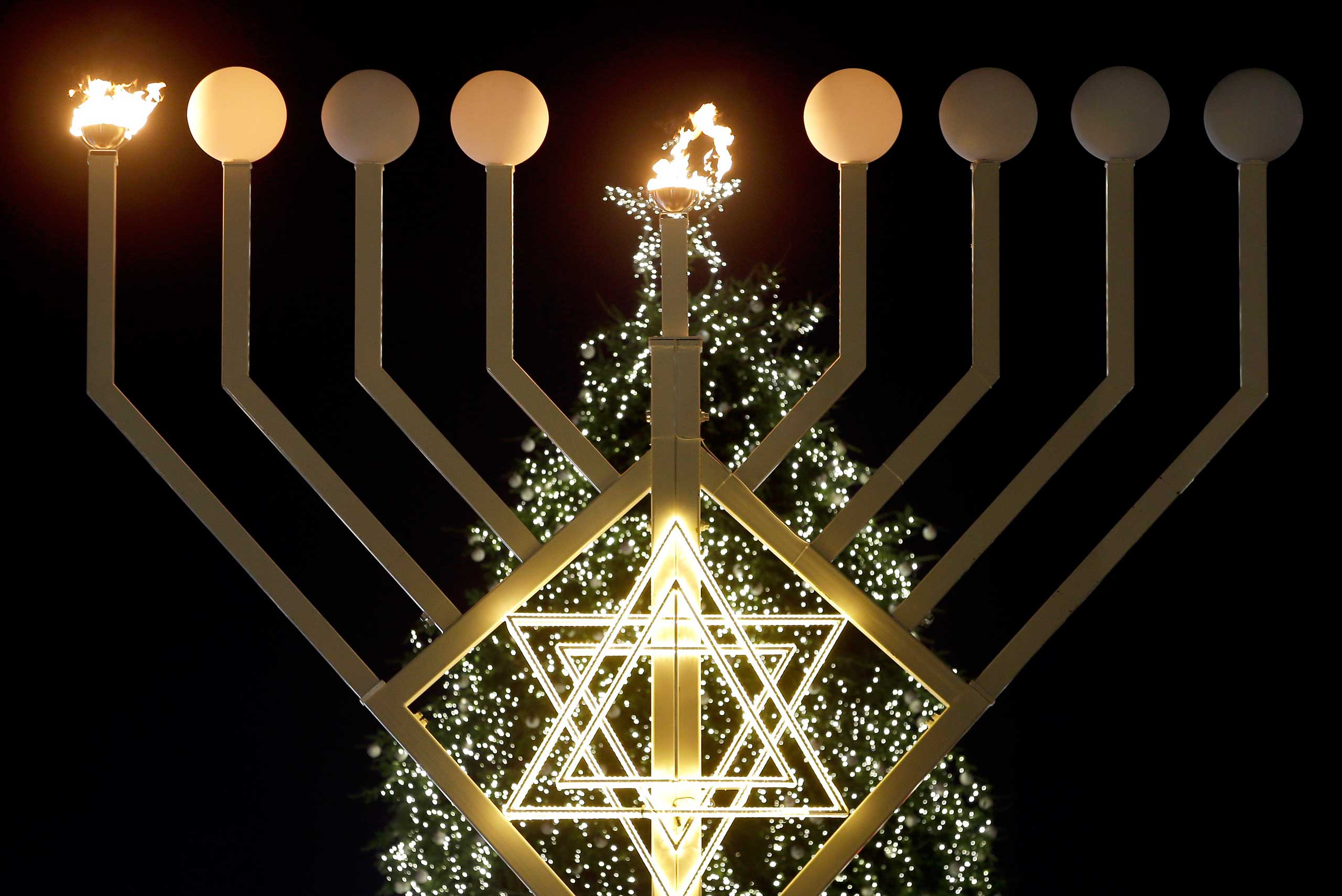 The first flames of a giant Hanukkah Menorah in front of a Christmas tree at the Brandenburg Gate in Berlin, Germany, Dec. 16, 2014.