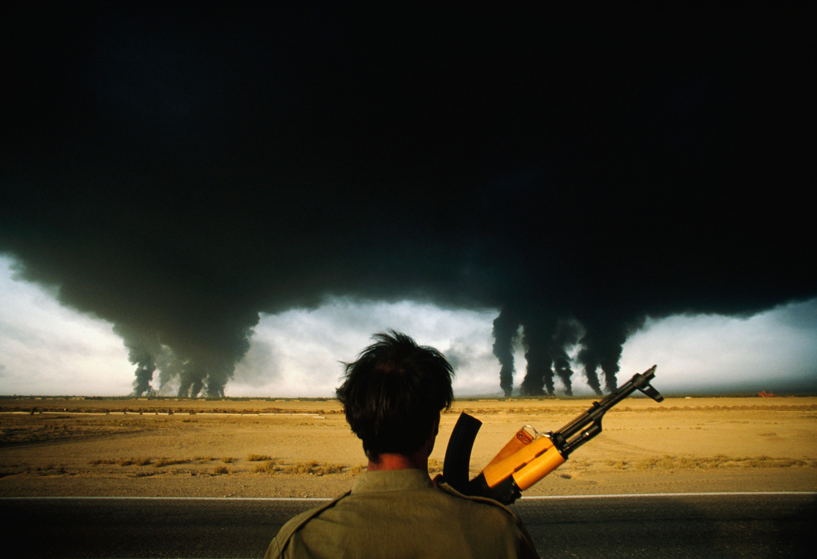 An Iranian soldier watches as smoke billows from multiple burning oil refineries in Abadan, Iran on Sept. 27, 1980.