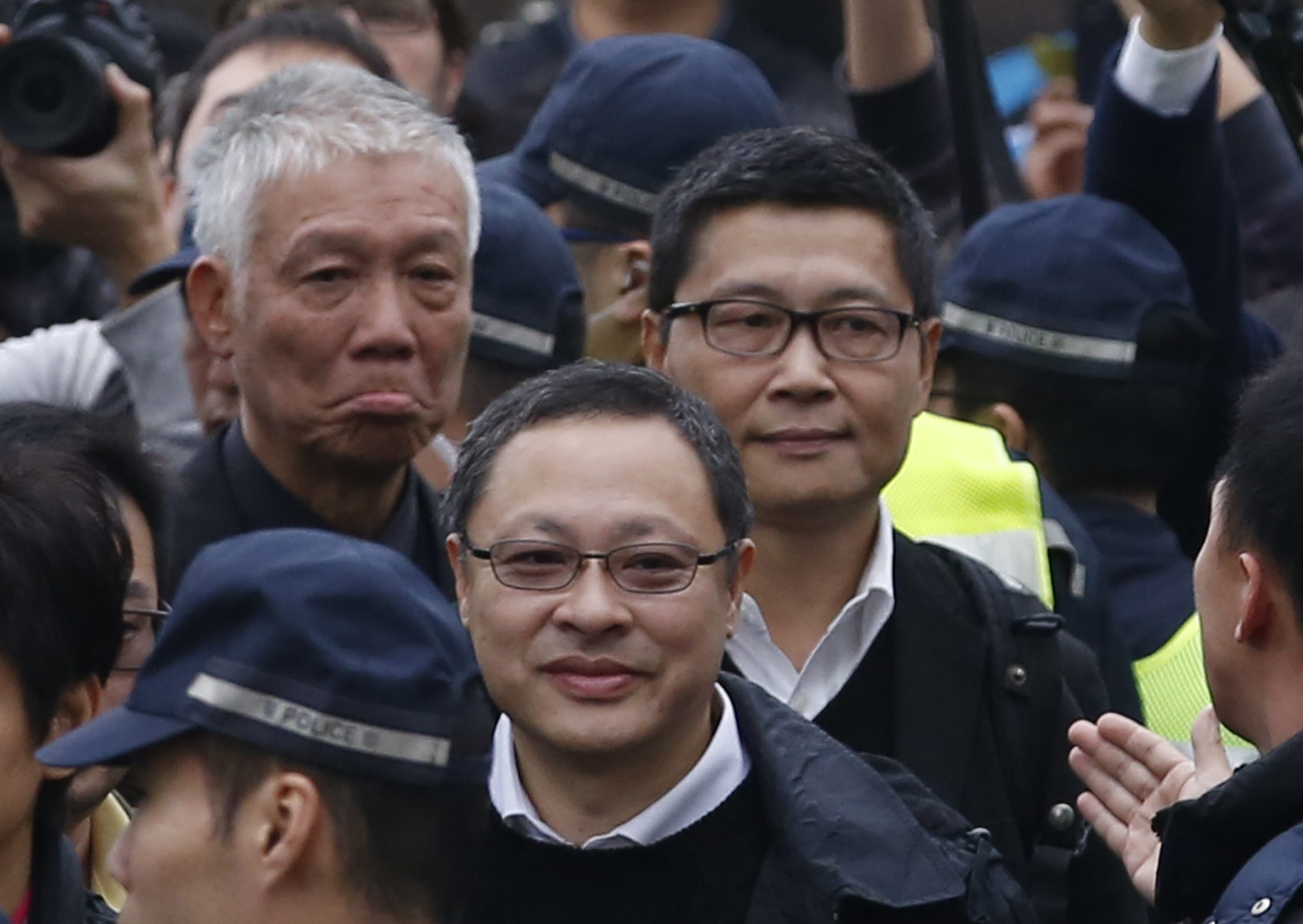 Three protest leaders, from right, Chan Kin-man, Benny Tai and the Rev. Chu Yiu-ming walk toward the police station in Hong Kong on Dec. 3, 2014, to surrender to police