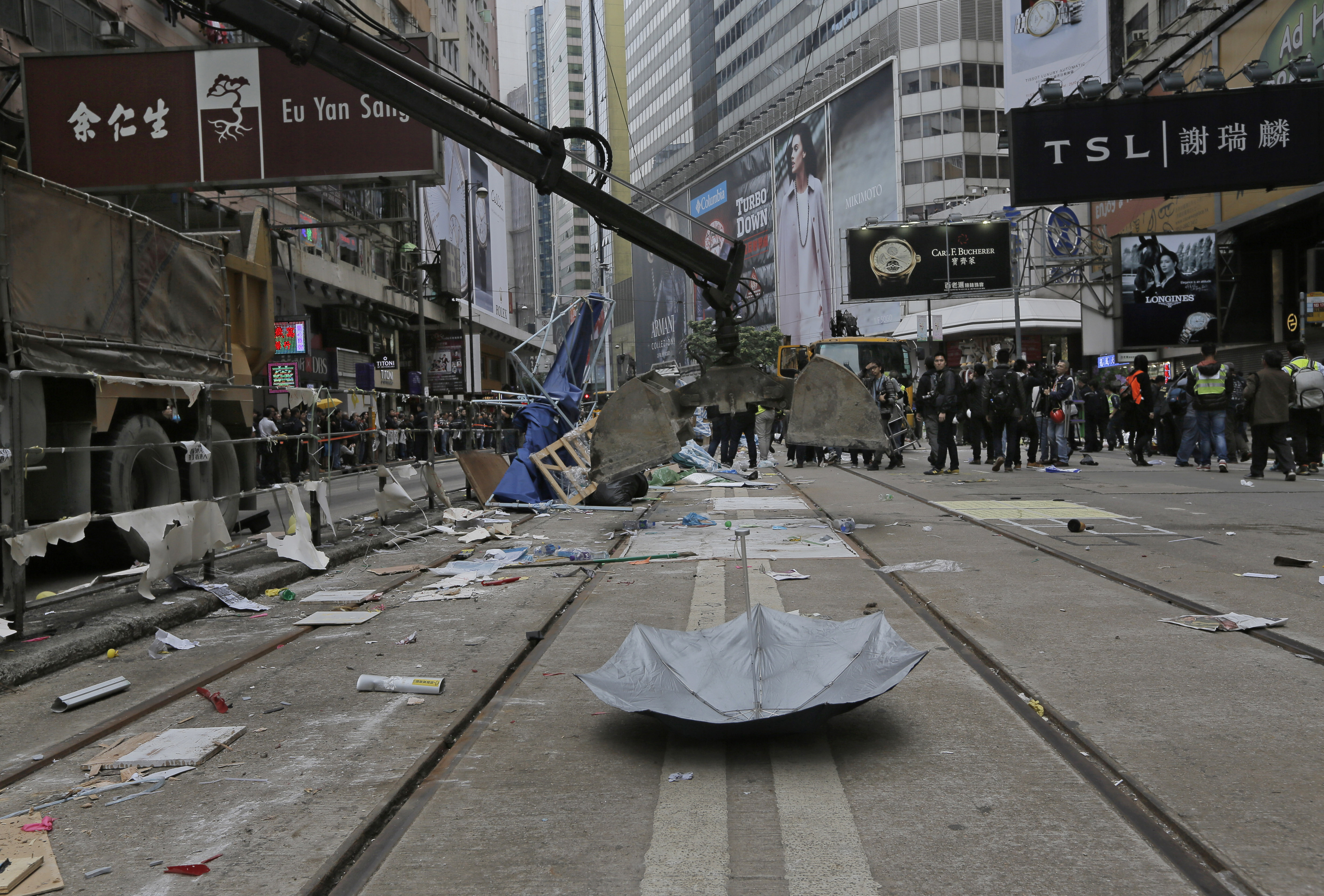 An excavation shovel is lowered to pick up an umbrella left behind by protesters as police clear barricades and tents on a main road in the occupied areas at Causeway Bay district in Hong Kong on Dec 15, 2014