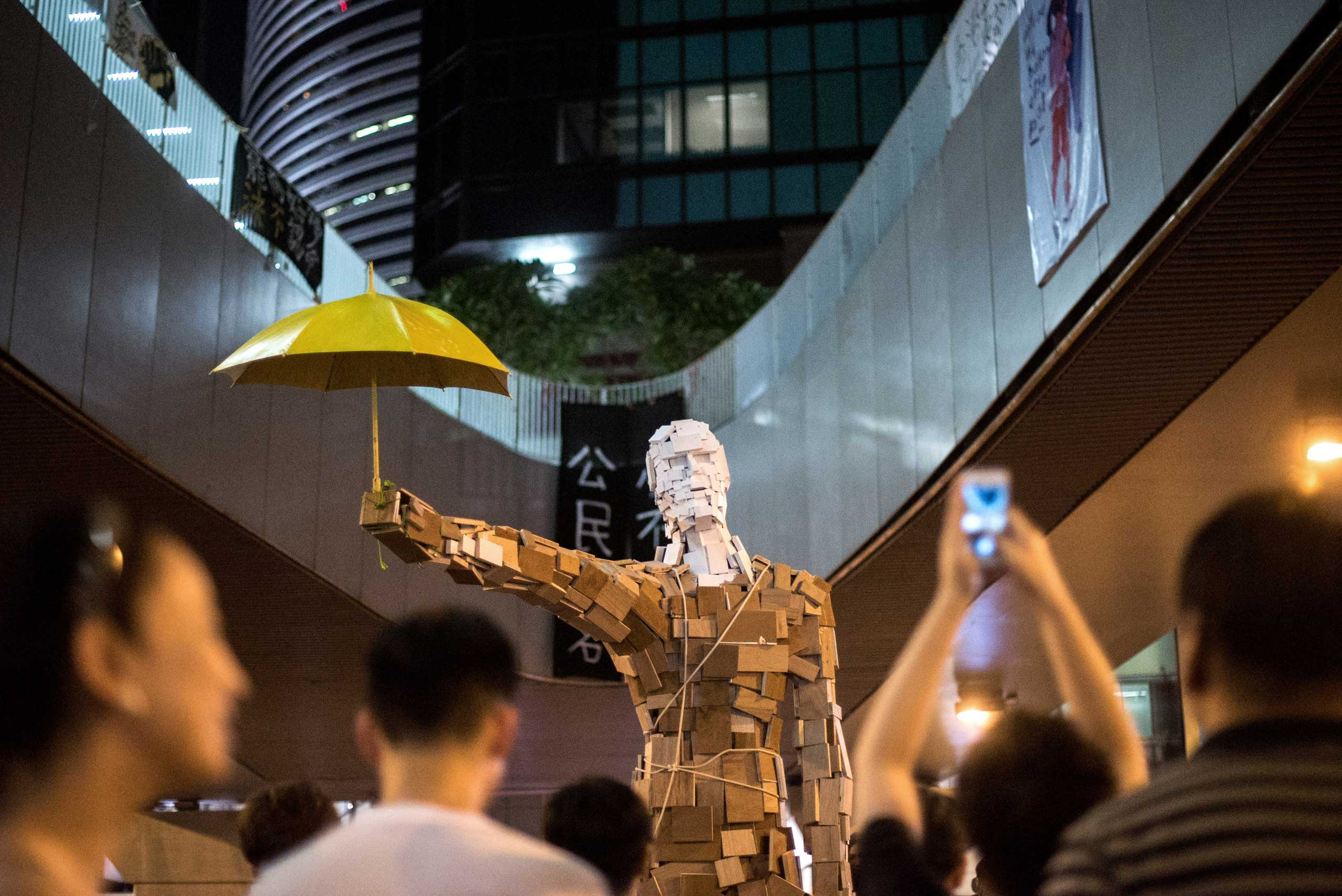 "The statue ""Umbrella Man"" by the Hong Kong artist known as Milk, is set up at a pro-democracy protest site next to the central government offices in Hong Kong on Oct. 5, 2014."