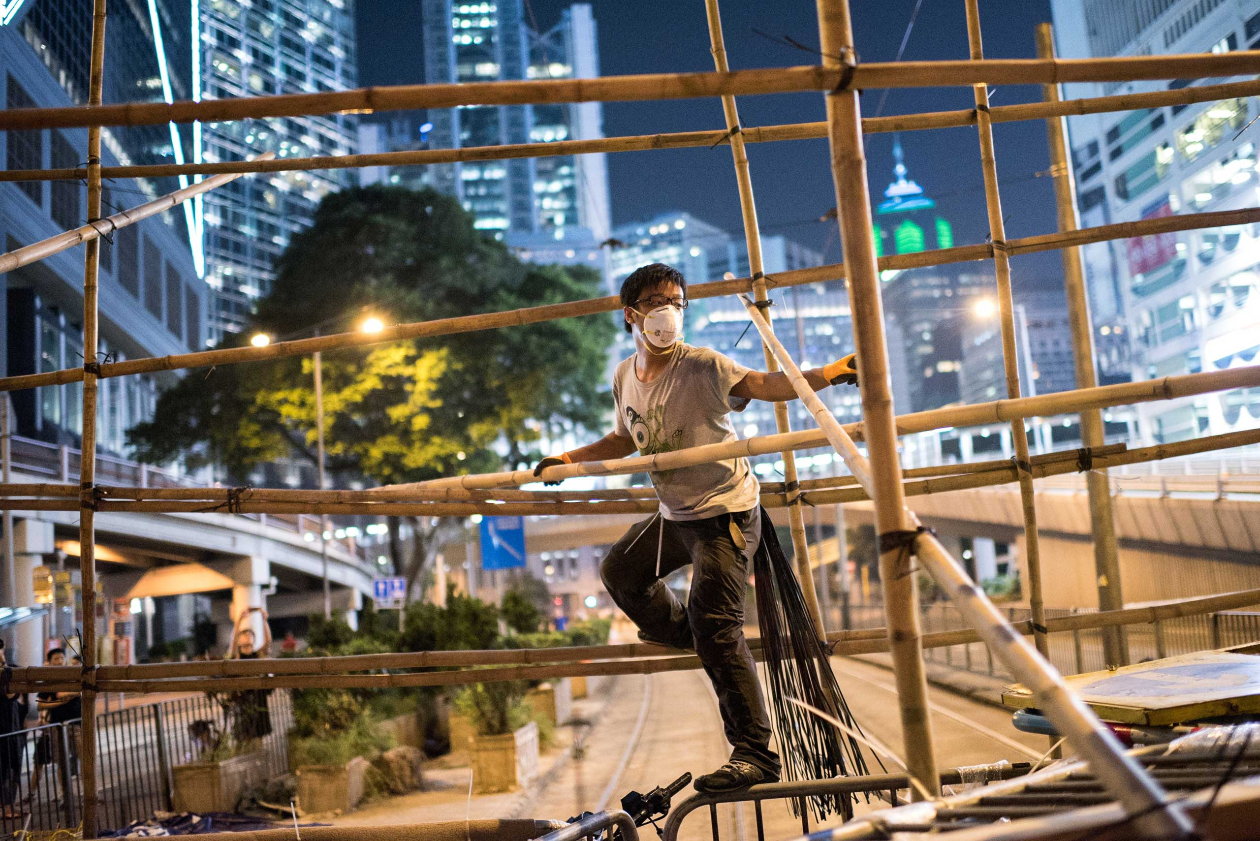 A pro-democracy protester uses bamboo to strengthen a barricade blocking a major road in Hong Kong on Oct. 13, 2014.