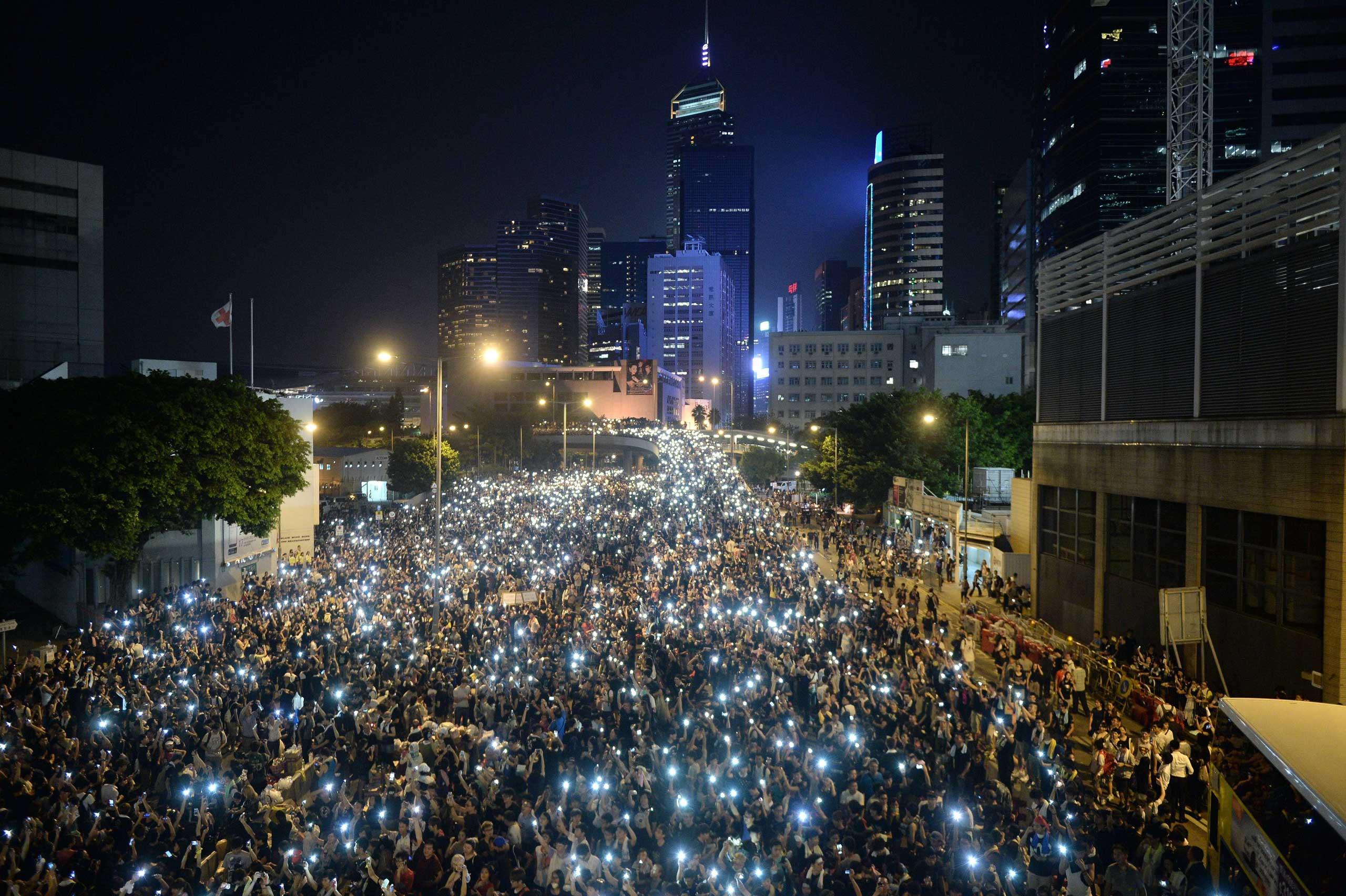 Pro-democracy demonstrators hold up their mobile phones during a protest near the Hong Kong government headquarters on Sept. 29, 2014.