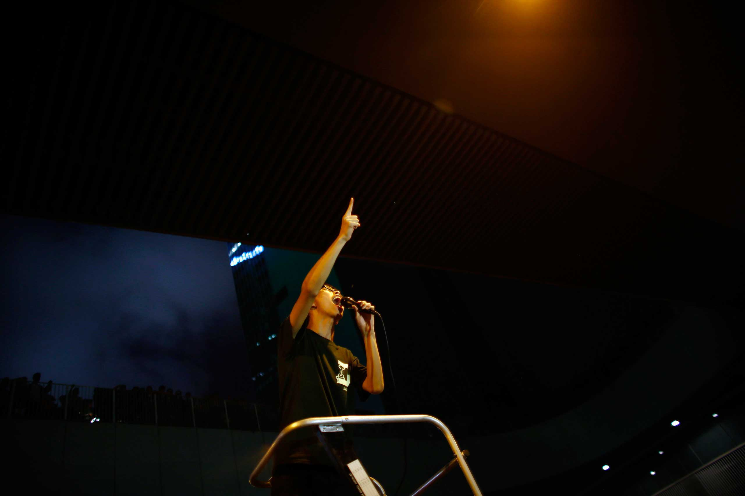 Joshua Wong, leader of the student movement, delivers a speech as protesters block the main street to the financial Central district, outside the government headquarters building in Hong Kong Oct. 1, 2014.